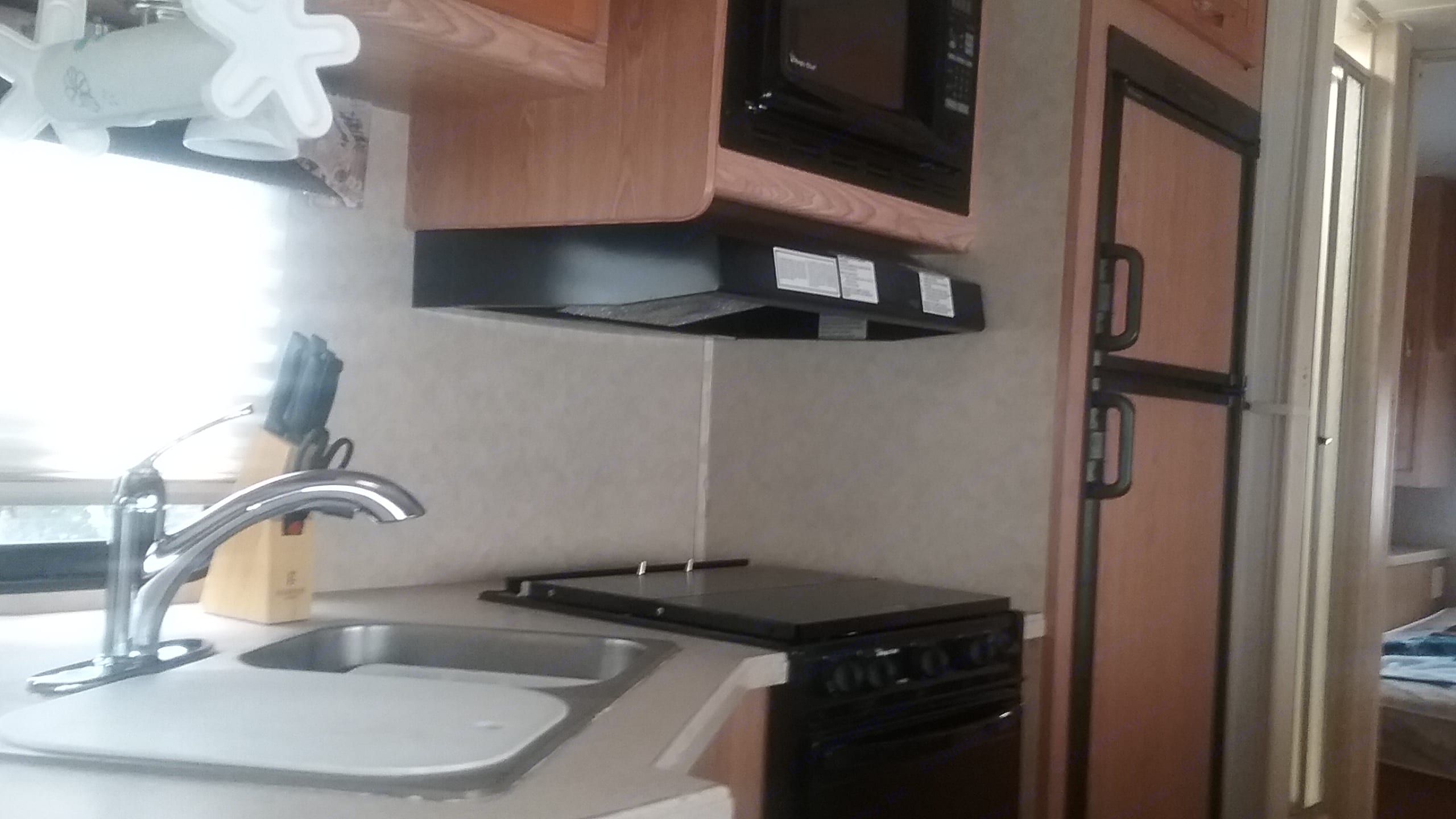 Kitchen area. Sink, stove, microwave, refrigerator,. Forest River Sunseeker 2006
