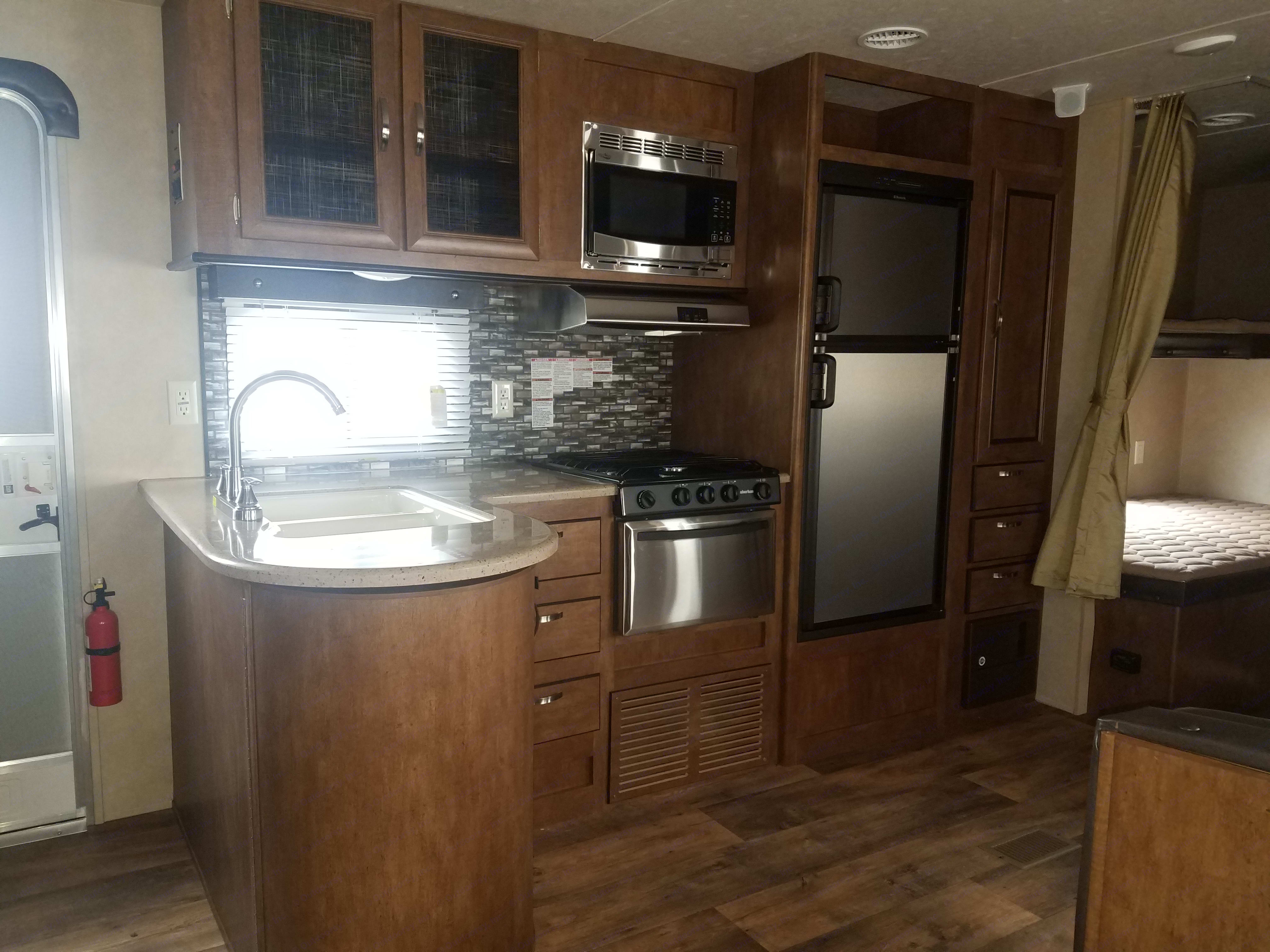 Kitchen with a double sink/microwave/fridge/stove/storage. Forest River Salem 2017