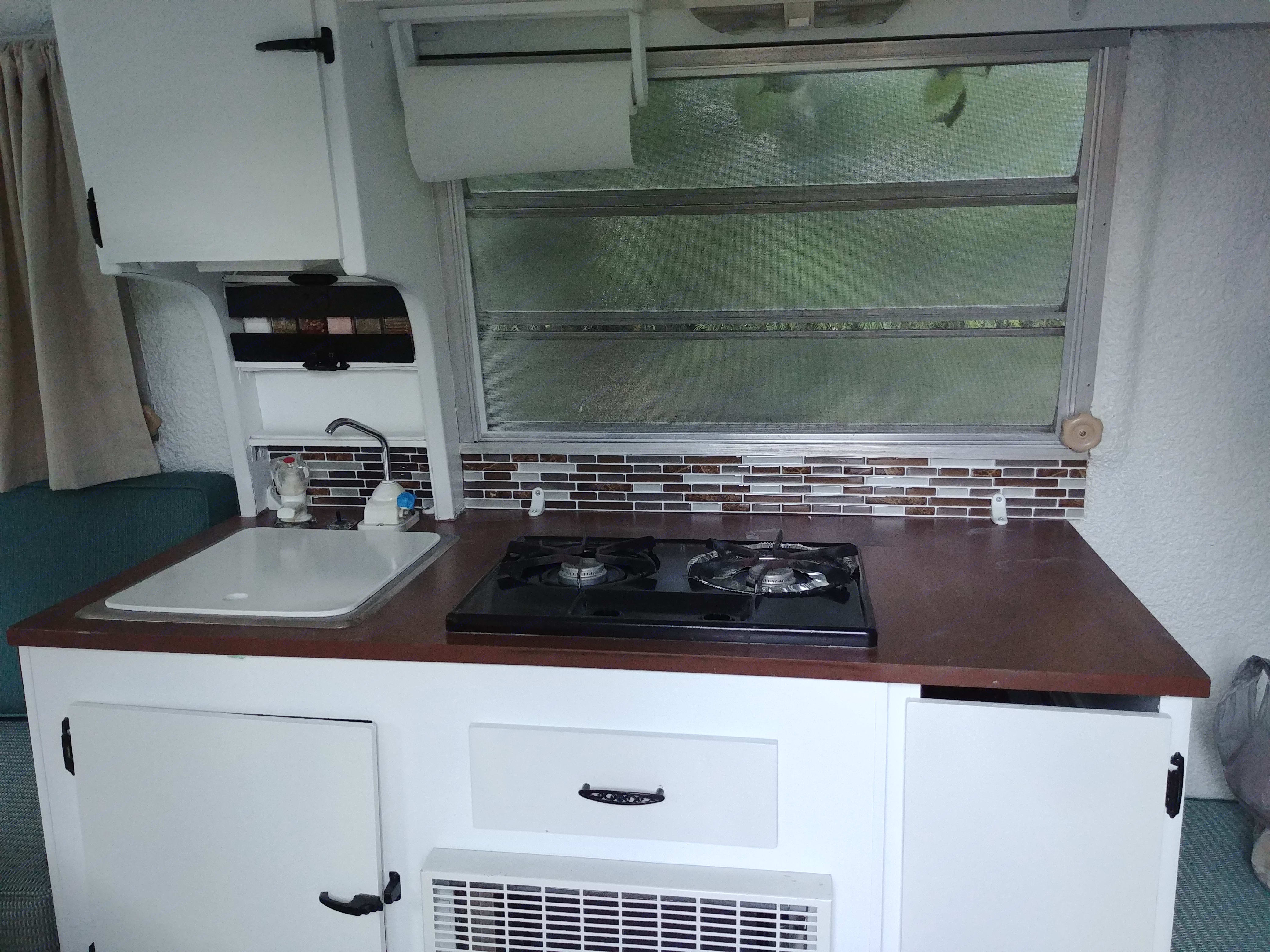 Sink with dual fawcets, 2 propane burner stove, a little backsplash to pull it all together, and, look above the sink is the spice rack!. Trillium Rv Jubilee 1981