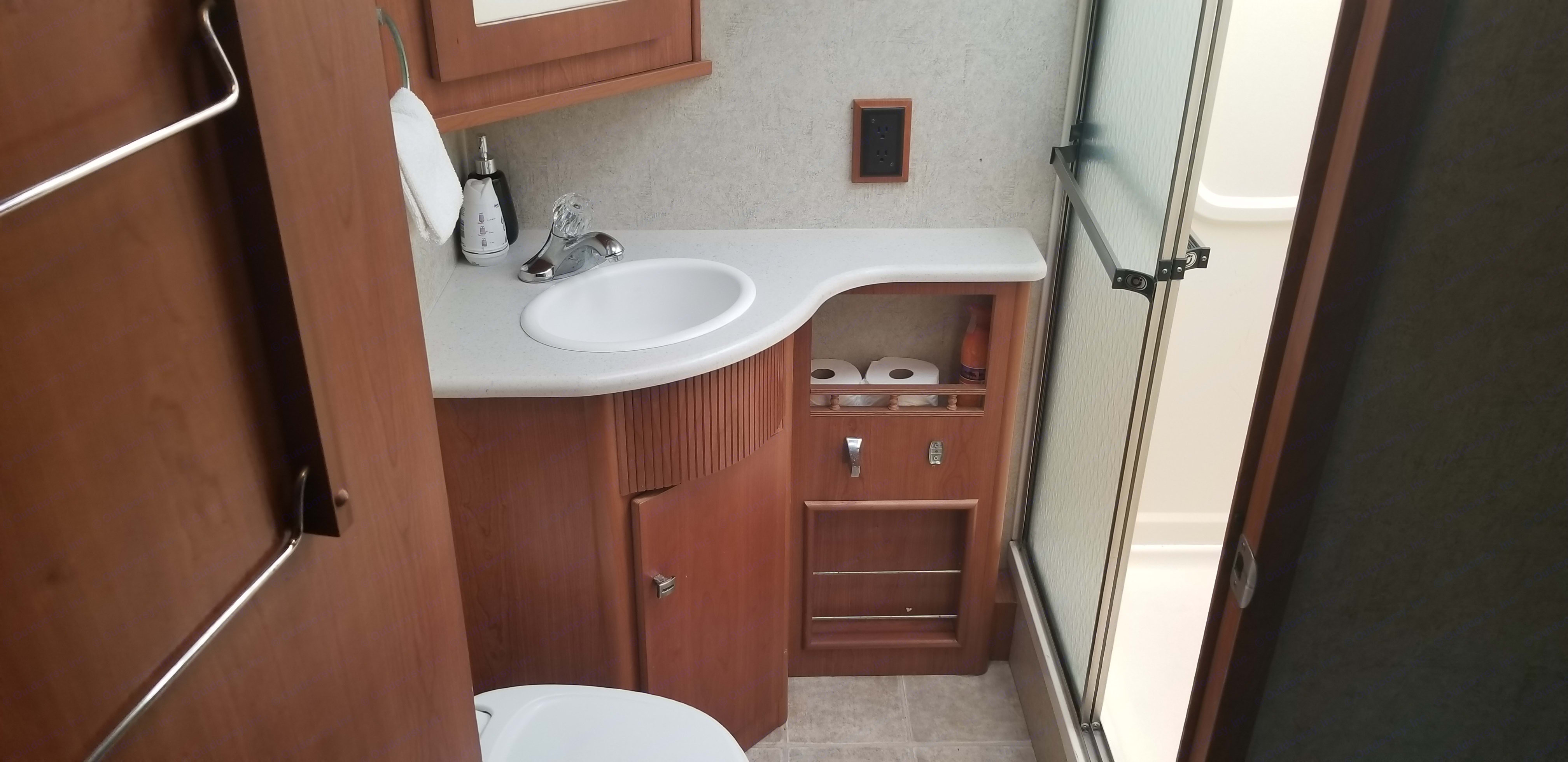 Full size bathroom with glass door walk in shower. Winnebago Sightseer 2008