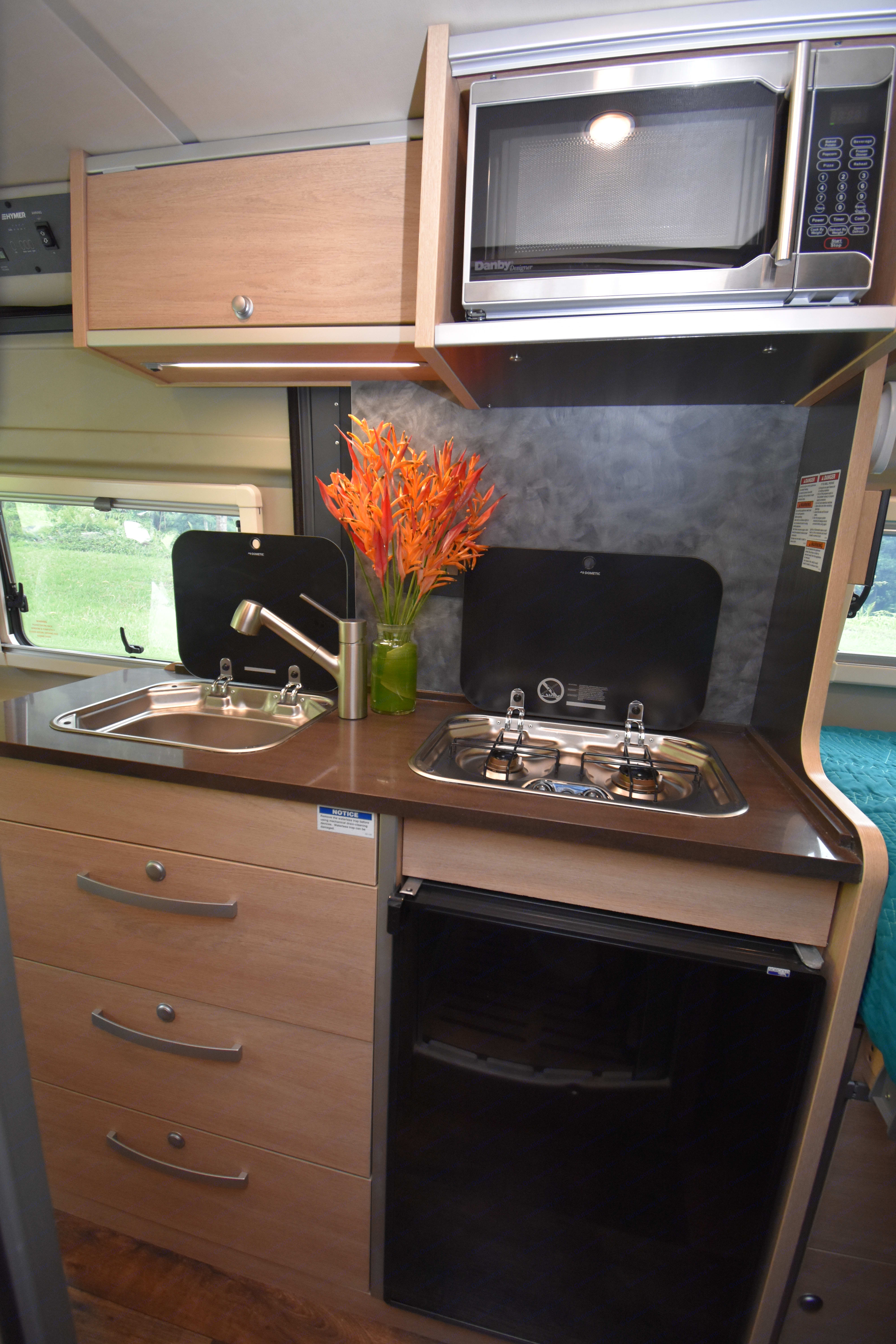 The feature-packed kitchen includes a sink, two burner stove, microwave, and refrigerator.. Hymer Aktiv 2018