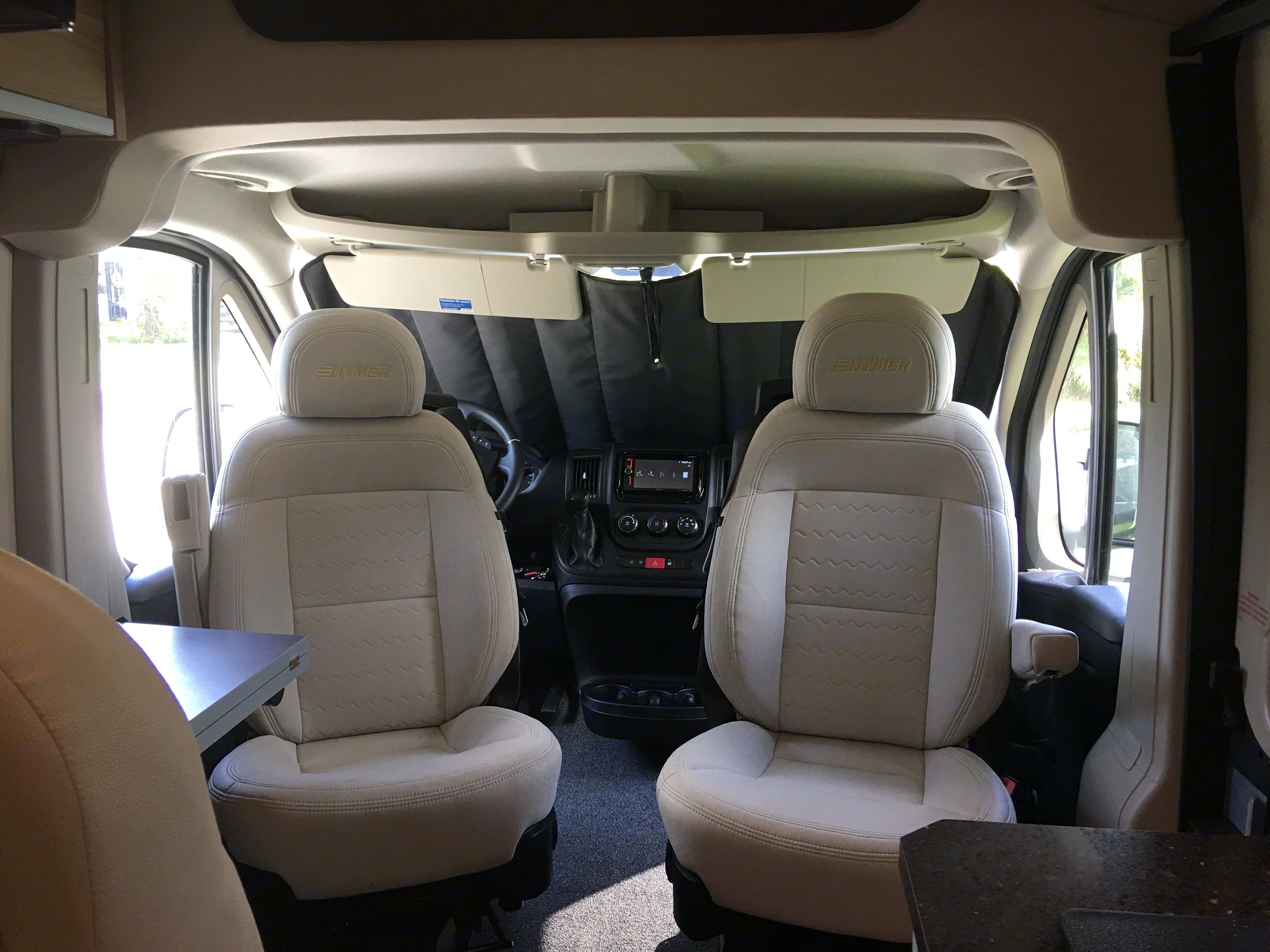 Driver and passenger captain chairs swivel to create lounge area. Full black out shades for front and sides windows keep coach private and cool. . Hymer Aktiv 2017