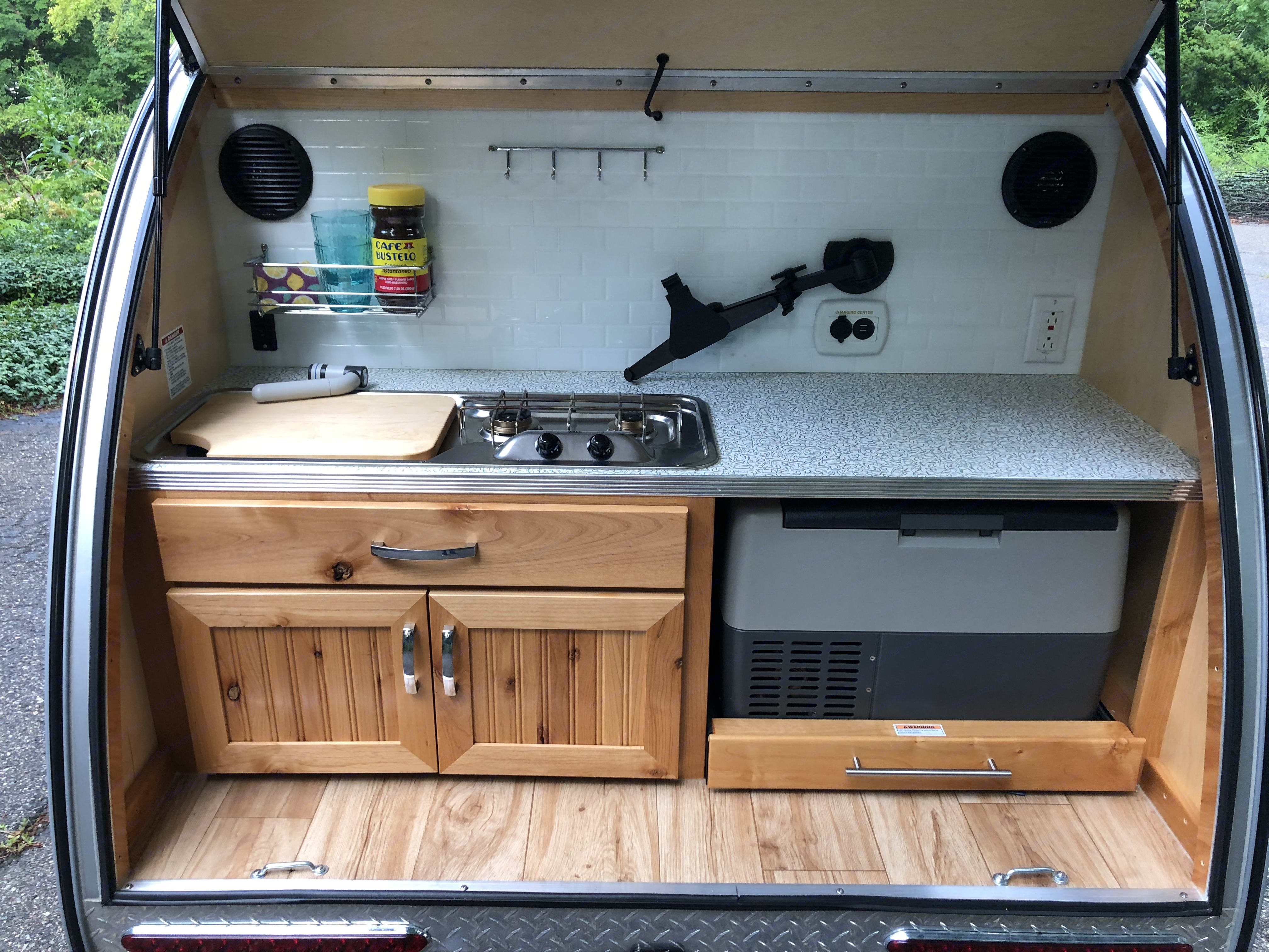 Rear galley kitchen has 2 burners, a sink, an electric fridge, and kitchen gear in the cabinet. . Little Guy Silver Shadow 2016