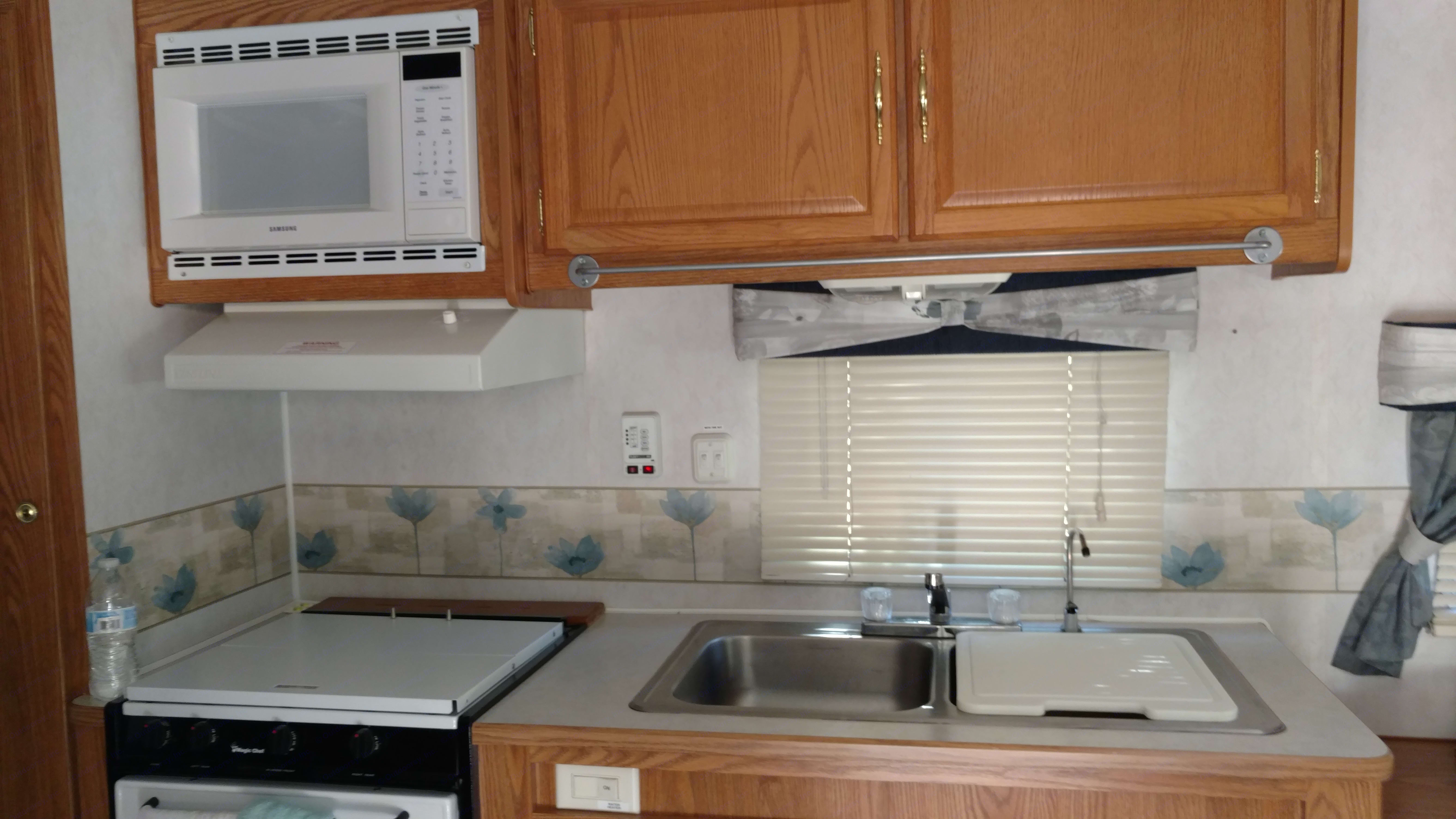 Fully functional kitchen with double sink, range top, oven, microwave, refrigerator, freezer and spacious cabinets.. Fleetwood Prowler 2002