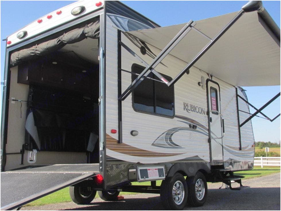 Will hold 2 ATVs and 1 dirt bike, or one small UTV. Ramp makes loading your toys a breeze. Tie down hooks in floor. Bed/couch combo folds flat against wall to haul toys. Once parked, open the back ramp and drop the screen to enjoy the nice fresh mountain air. . Dutchmen Rubicon 2015