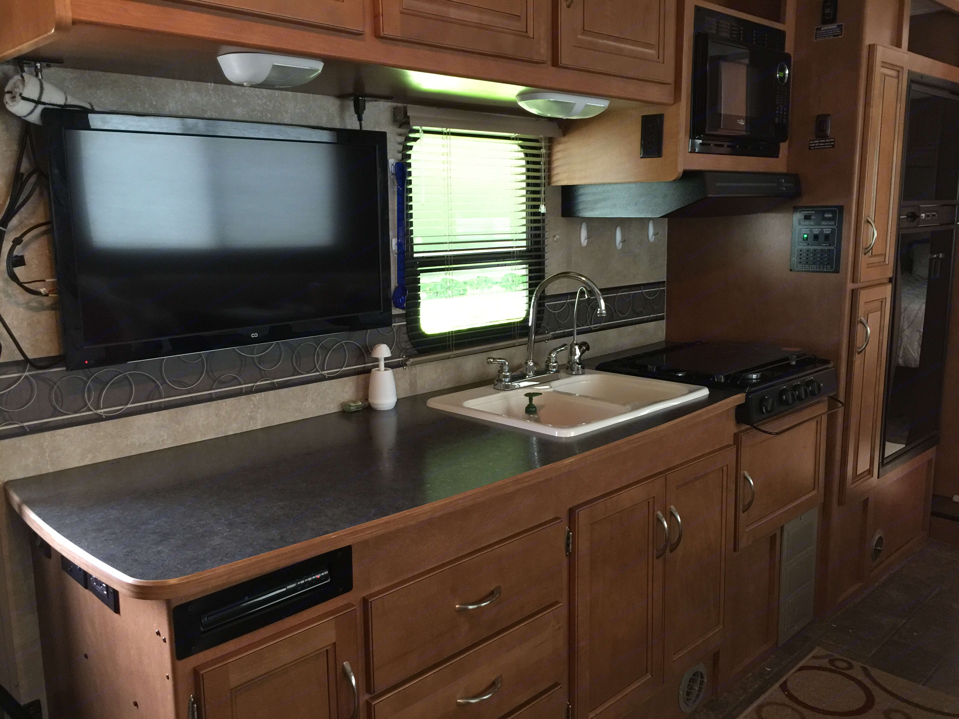 kitchen with pantry, refrigerator, microwave, 3-burner gas stove top TV, dvd player. Winnebago Minnie Winnie 2014