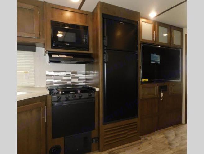 Kitchen with refrigerator, stove, sink microwave. Keystone Cougar Half-Ton 2019