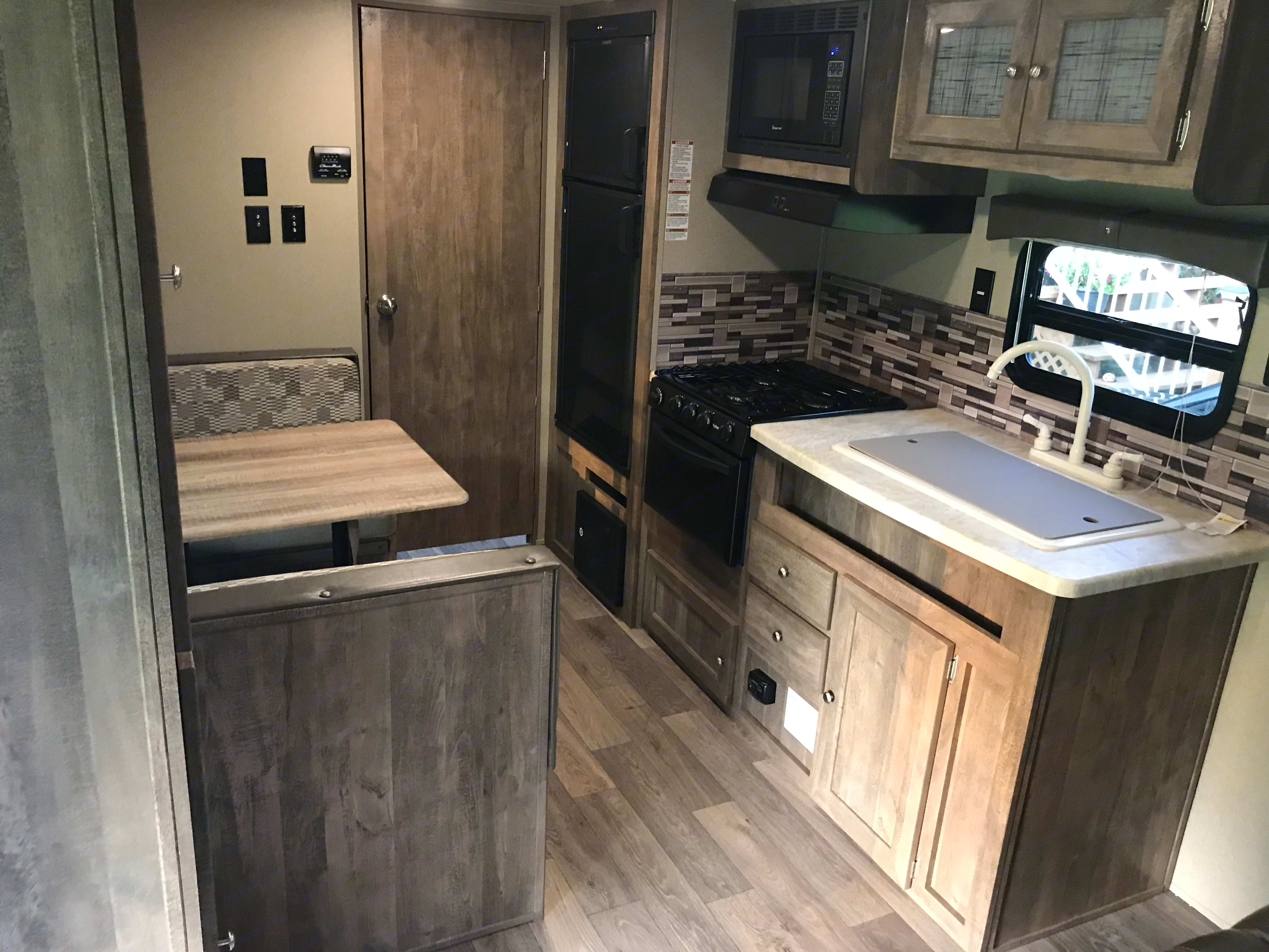 Enjoy a full kitchen Fridge and freezer, microwave, 3 burner range, oven, double sink, table seats 4-6 people. Table folds down to a double bed.. Forest River Puma 2018