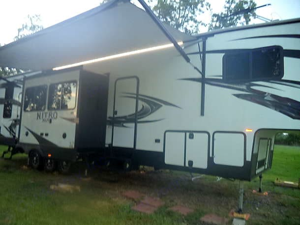 Living room w/ slide and awning extended  . Forest River Nitro XLR 2017