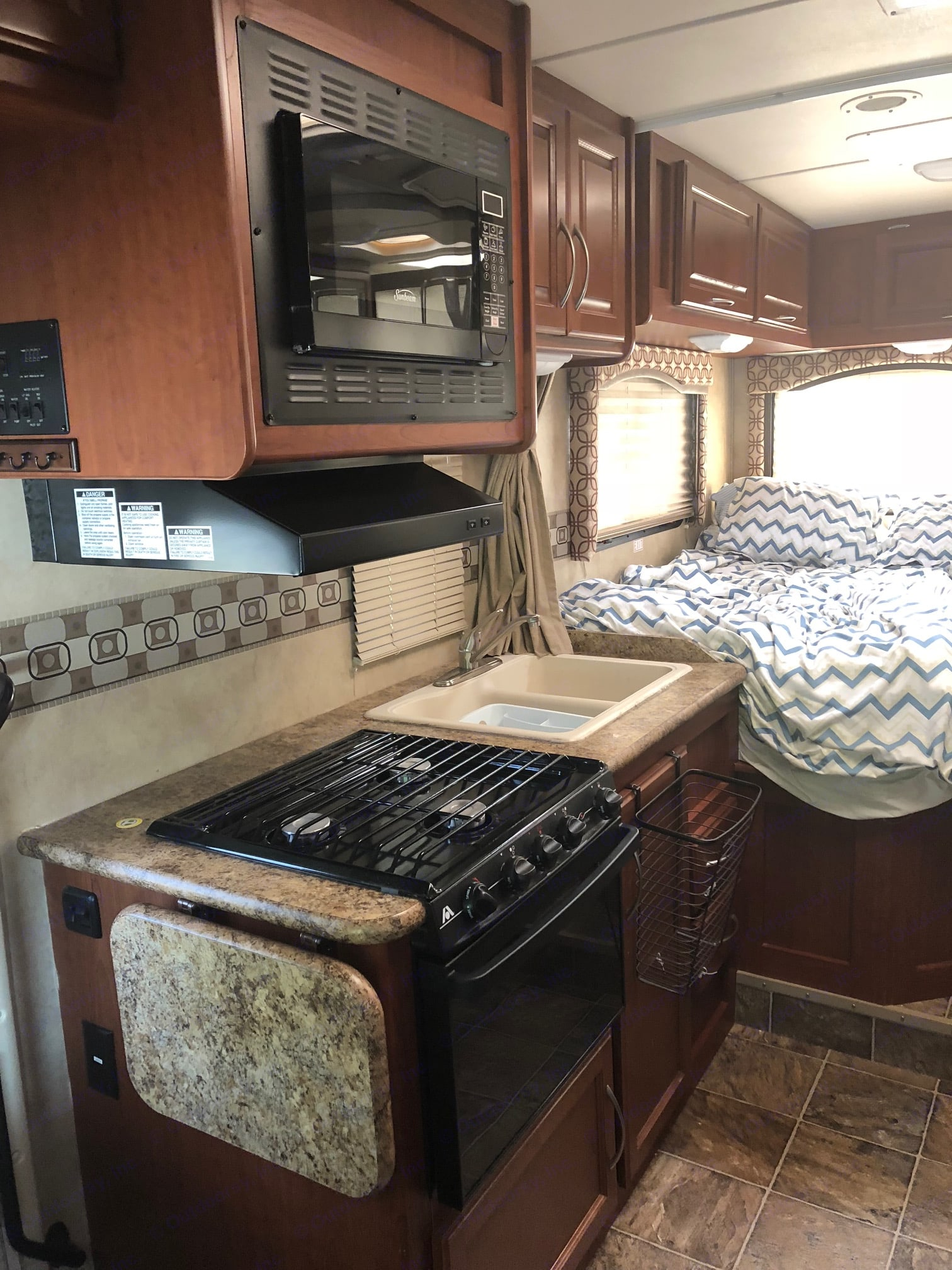 Kitchen is equipped with: stove, oven, microwave fridge and sink. . Thor Motor Coach Four Winds 2011