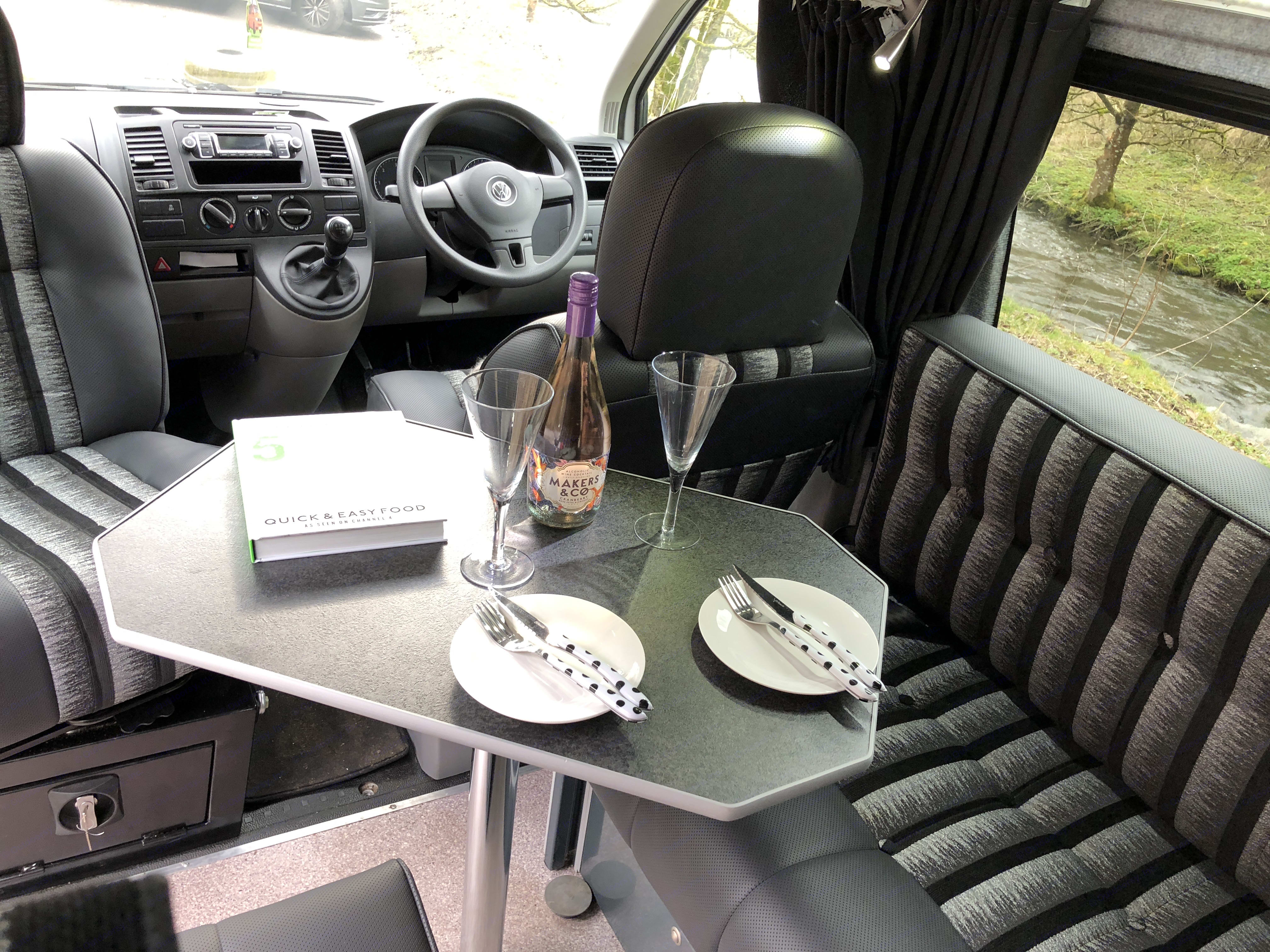 Interior lounge area with swivel passenger seat and dining table.. Volkswagen T5 Vivante 2015