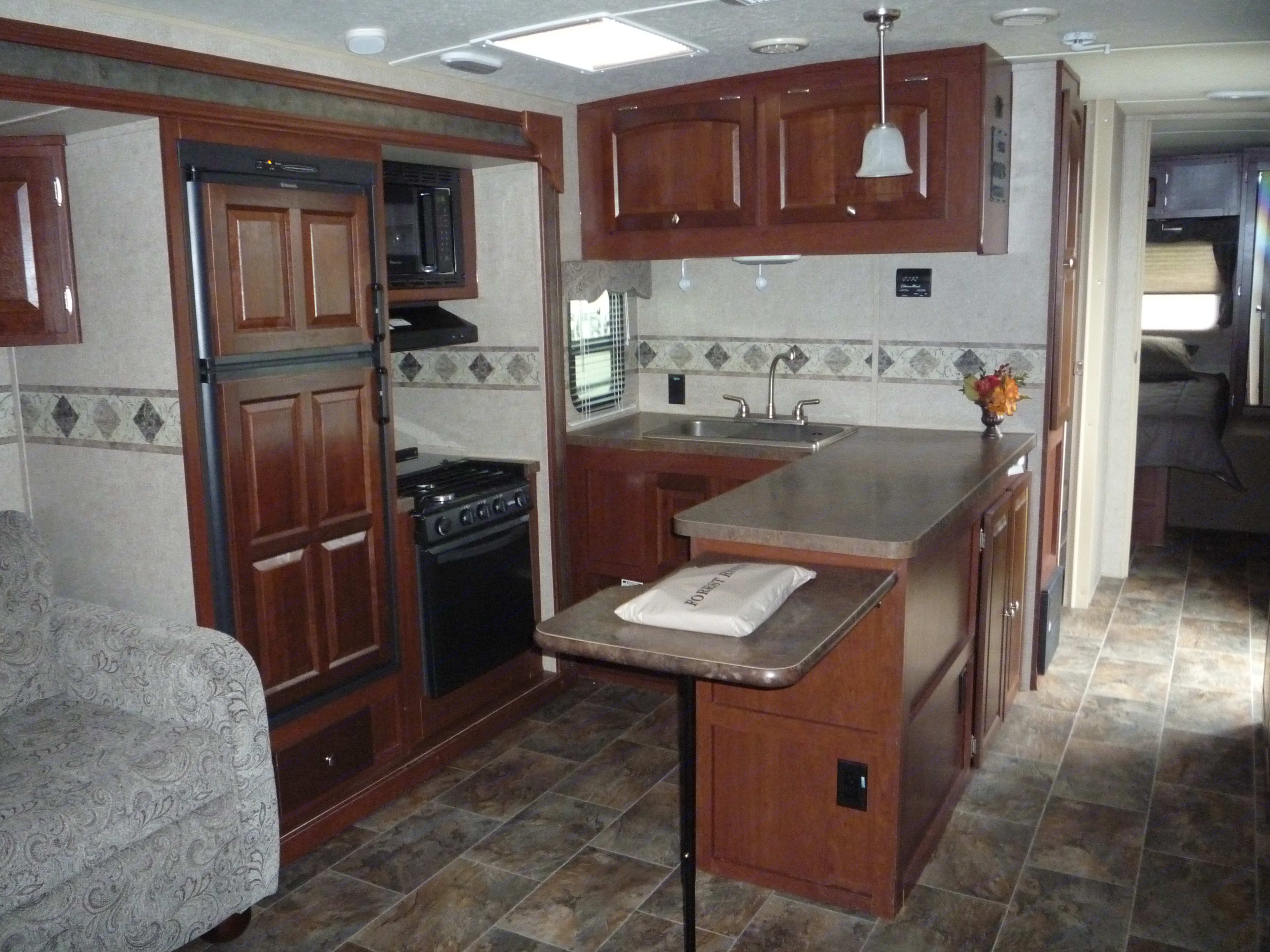U Shaped Kitchen Refrigerator, Gas Oven, Stove Top, and Microwave, fully stocked with kitchenware. Forest River Rockwood Ultra Lite 2014