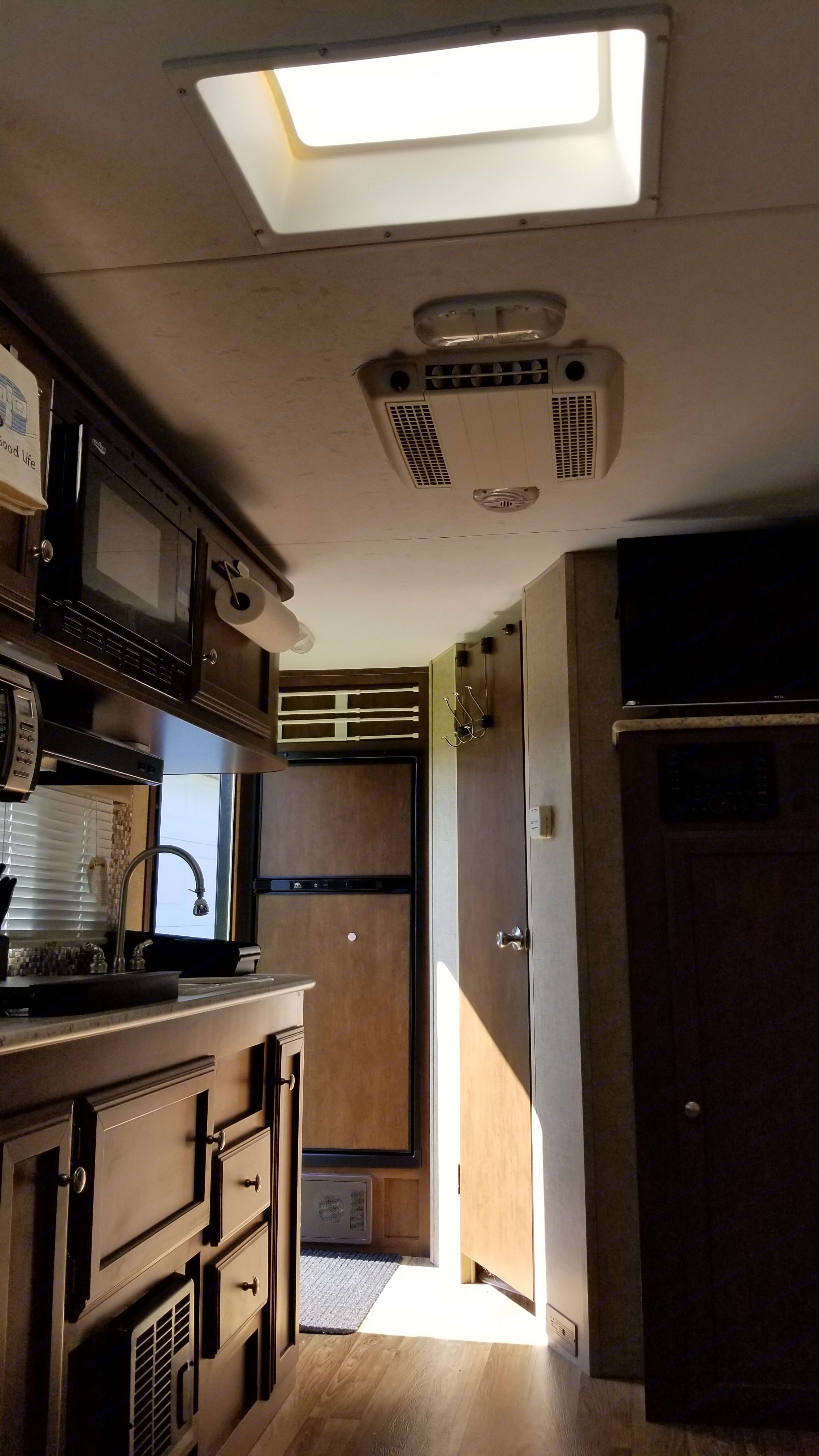 View from the bed of fridge, bathroom, kitchen, TV. Venture Rv Sonic 2015