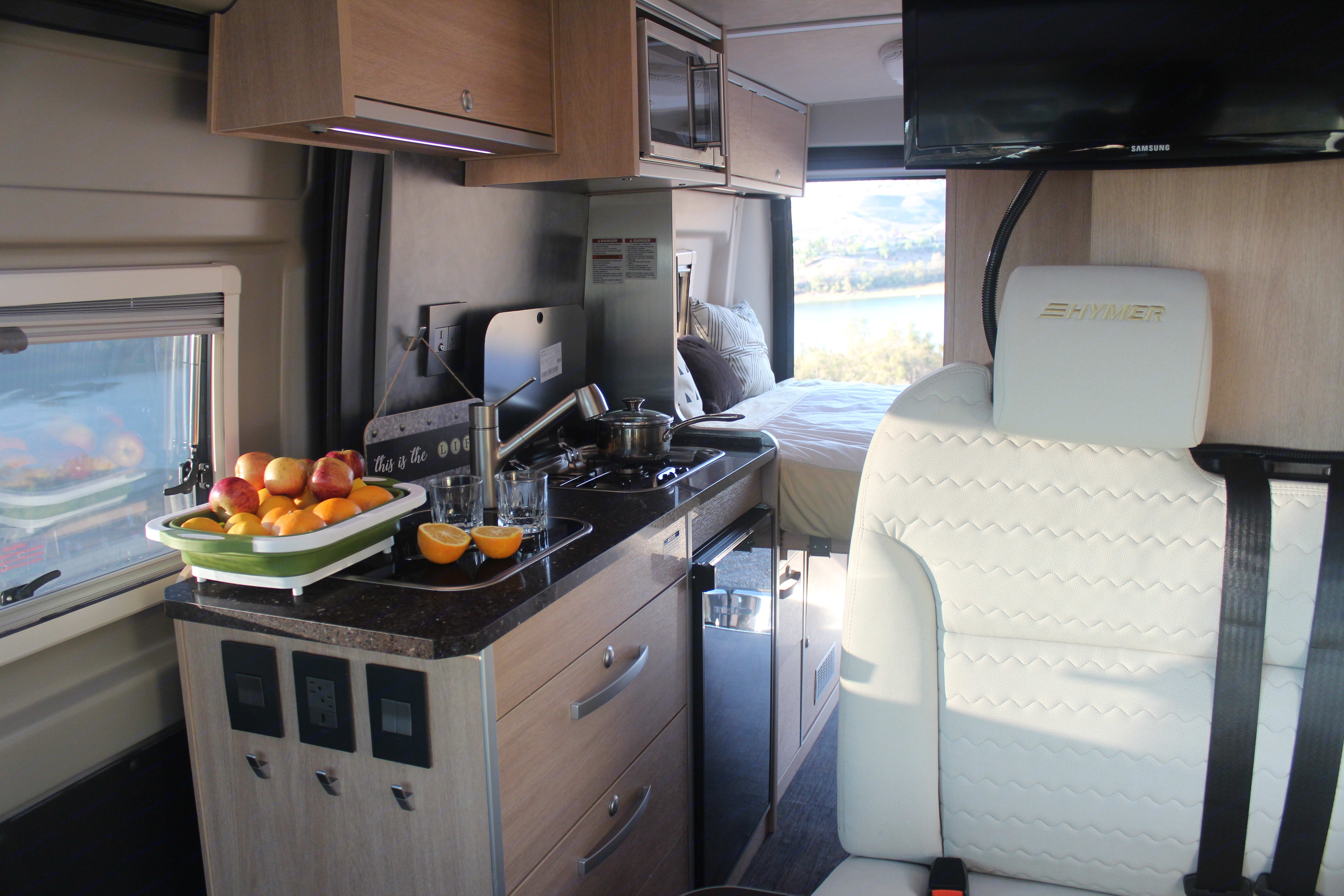 Kitchen galley area features a microwave, dual burner propane stove, and pull out faucet which can also be used as an outdoor shower.  . Hymer Aktiv 1.0 2018