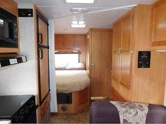 Queen bed with privacy sliding door which includes bathroom . Forest River Sunseeker 2009