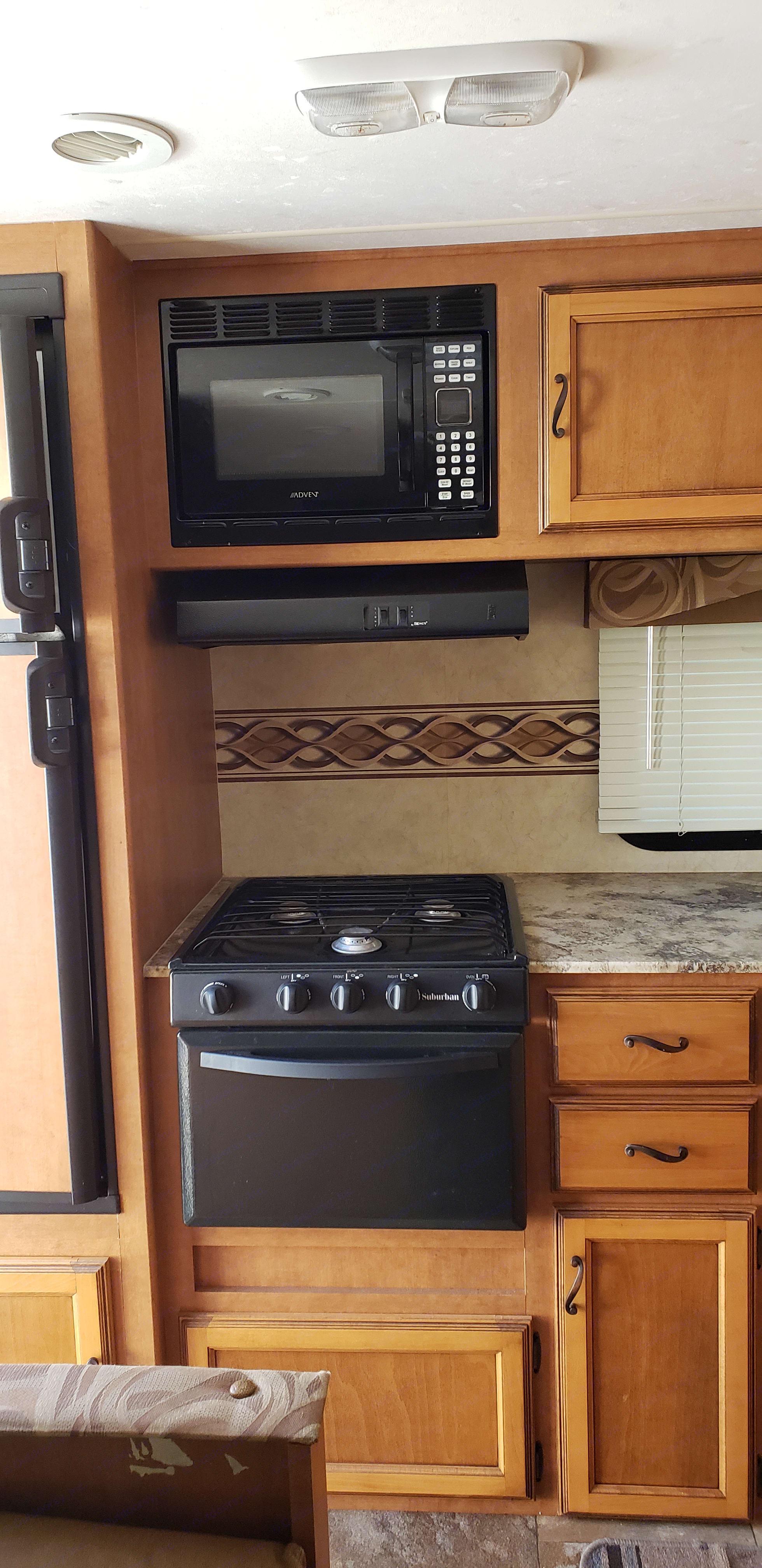 Kitchen that includes stove, microwave,  and fridge. Coachmen Apex 2013