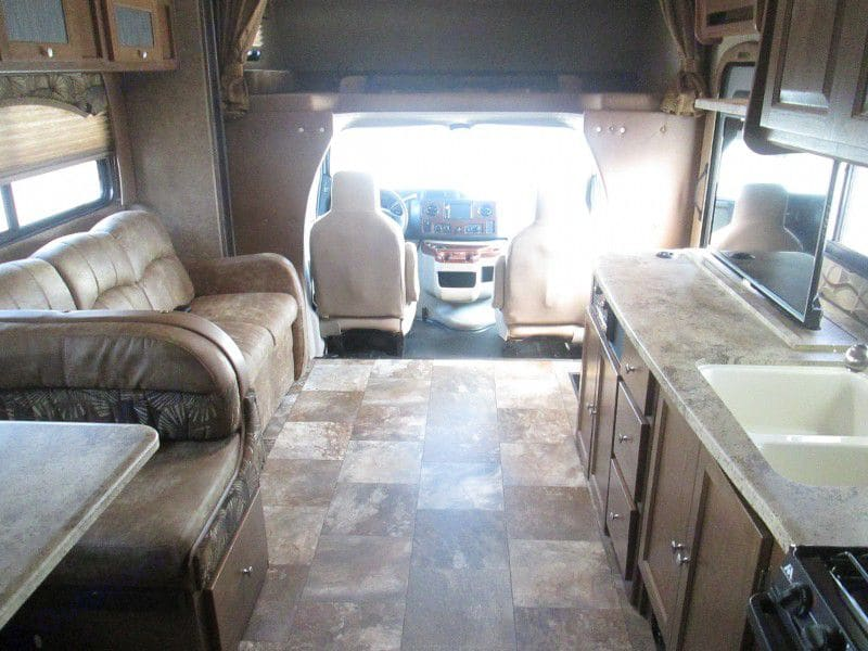Couch and TV viewing area.   Couch make a sleeping bed for smaller children.. Coachmen Leprechaun 2016