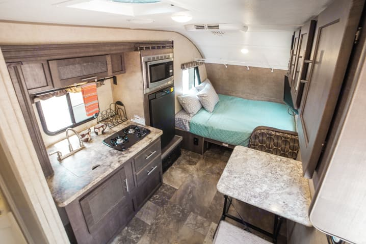 Interior of trailer. Amenities include queen bed, kitchen slide-out, and a dinette set that folds down into second bed.  . Forest River R-Pod 2016