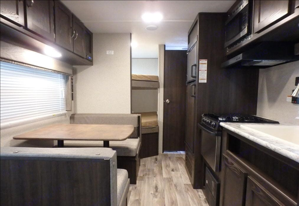 This photo shows the dining table that makes into a small bed about 4 feet long. The two bunk beds are 4 inches narrower than a full size bed. . Keystone Springdale 2018
