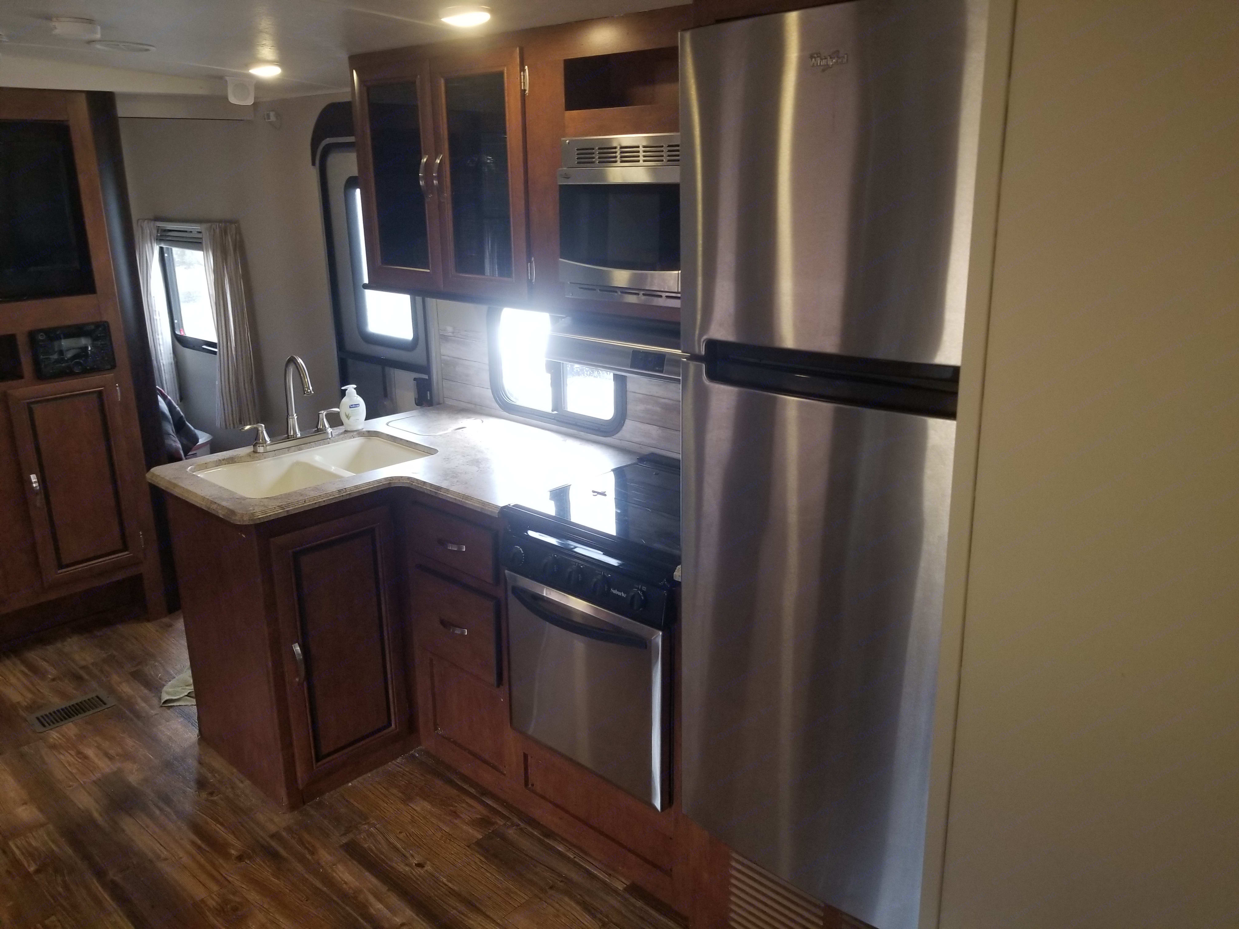 Residential fridge with plenty of room, three burner stovetop with oven and microwave.  . Forest River Vibe 2017