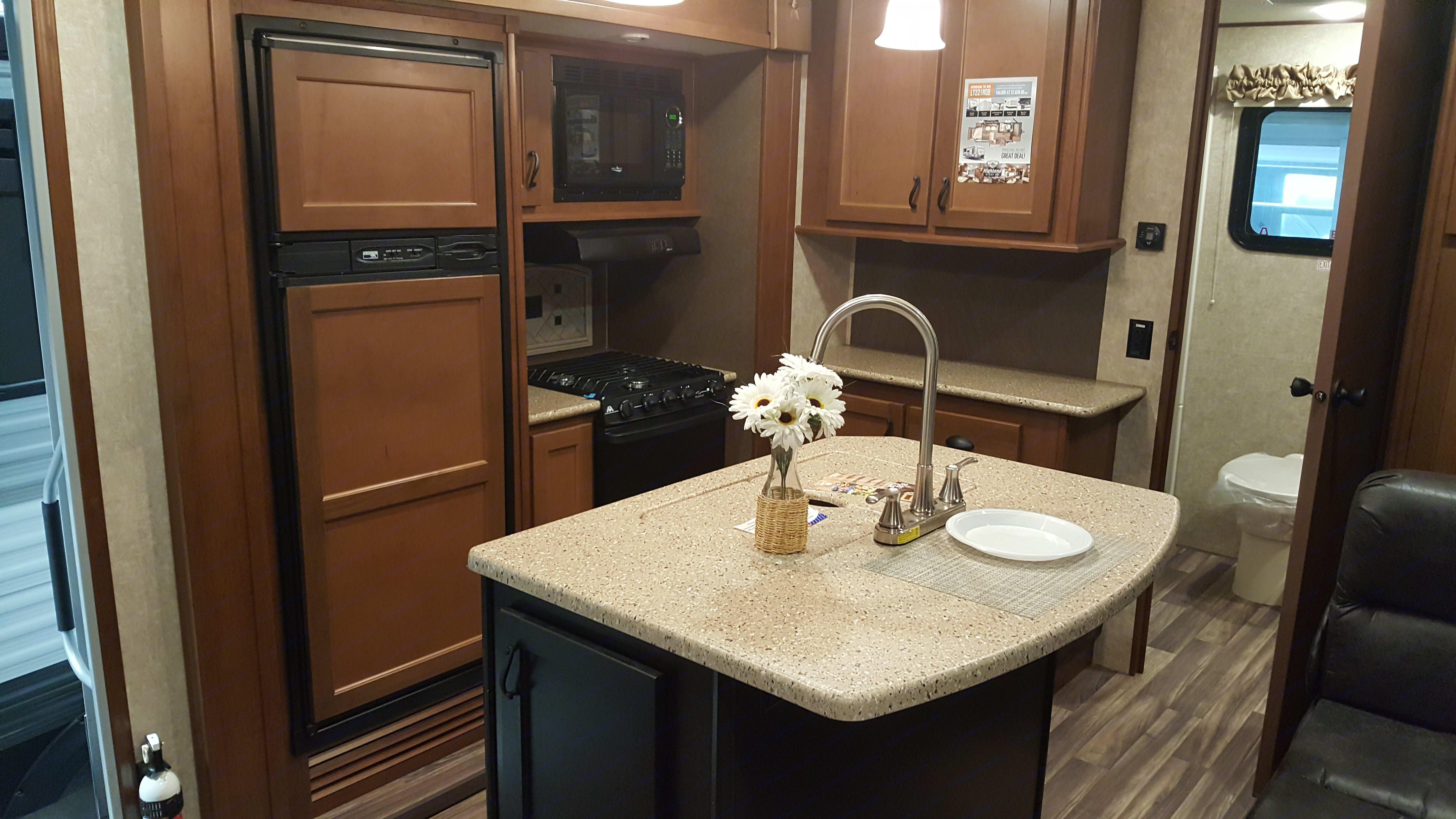 Full kitchen with large fridge/freezer, stove, oven island with lots of storage.. Open Range Light 2017