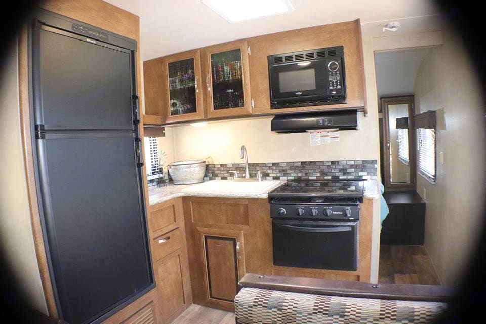 Full kitchen with sink, stove, refrigerator, some pots and pans, and silverware.. Forest River Wildwood 2017