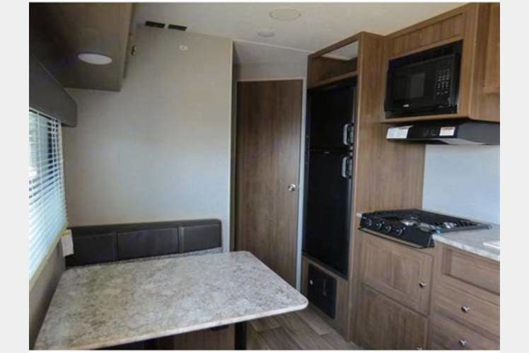 Full kitchen with foldable kitchenette that turns into a bed! . Dutchmen Aspen Trail 2019