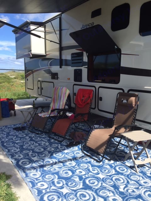 life is a beach, storage with plenty of chairs,automatic steps which you can set to manual in control center after you setup RV, automatic leveling from drivers side which is to be done before slideouts are activated, for dry camping/onboard generator. . Jayco Precept 2015
