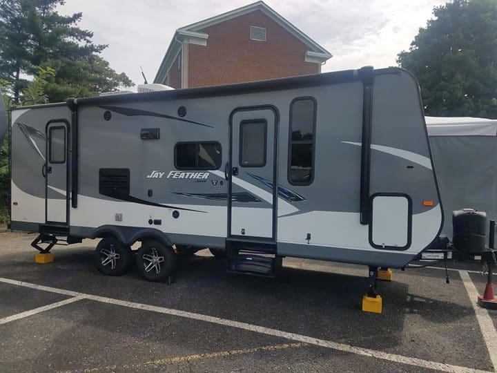 Side view highlights the two entrances to the trailer. This side of the camper has a TV mount with cable and power hookups and a storage compartment. . Jayco Jay Feather 2016