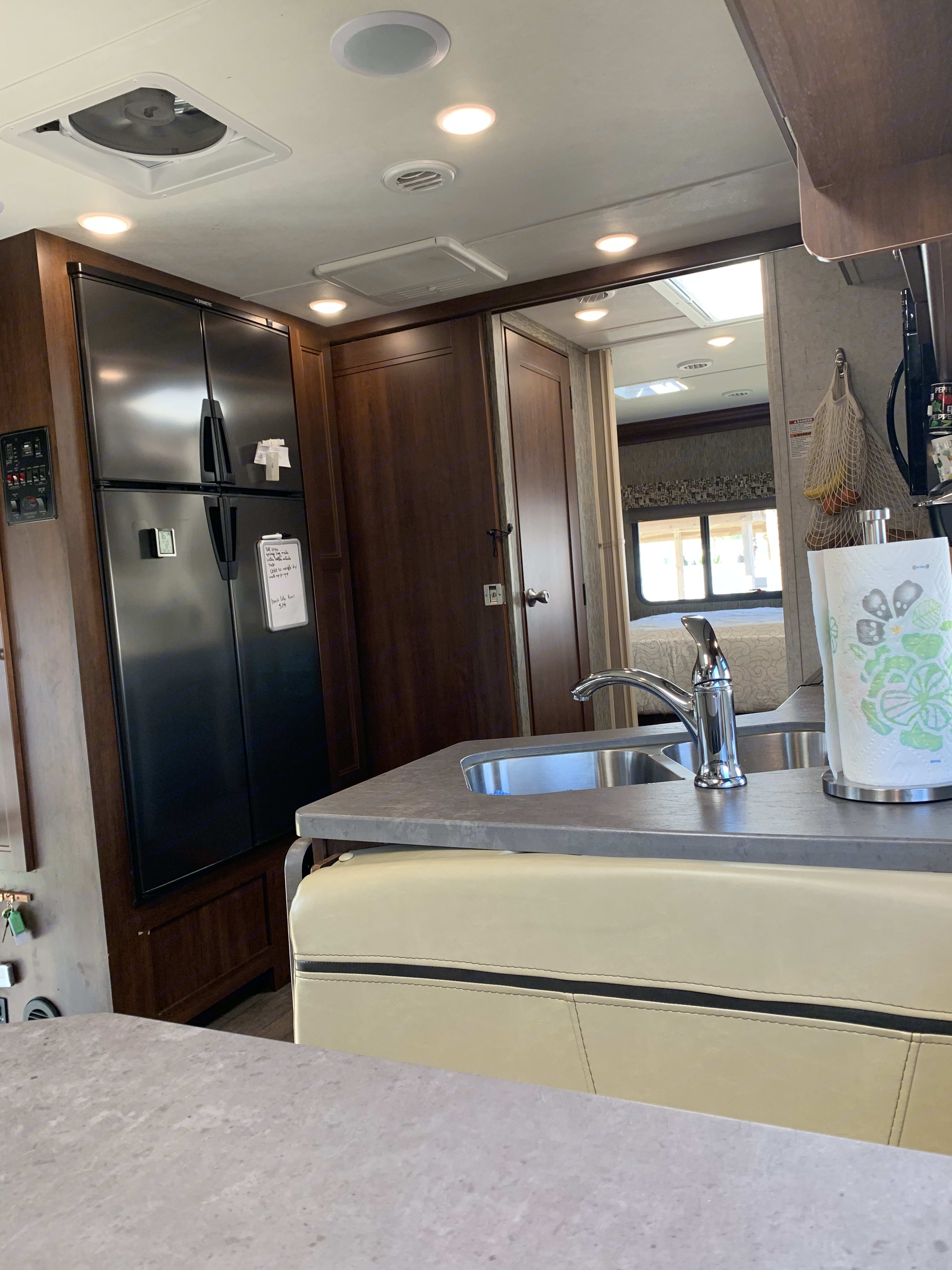 Dometic 12 Cu. ft. four door refrigerator with ice maker with pantry next to it. Rolling privacy door for bedroom. . Forest River Sunseeker 2018