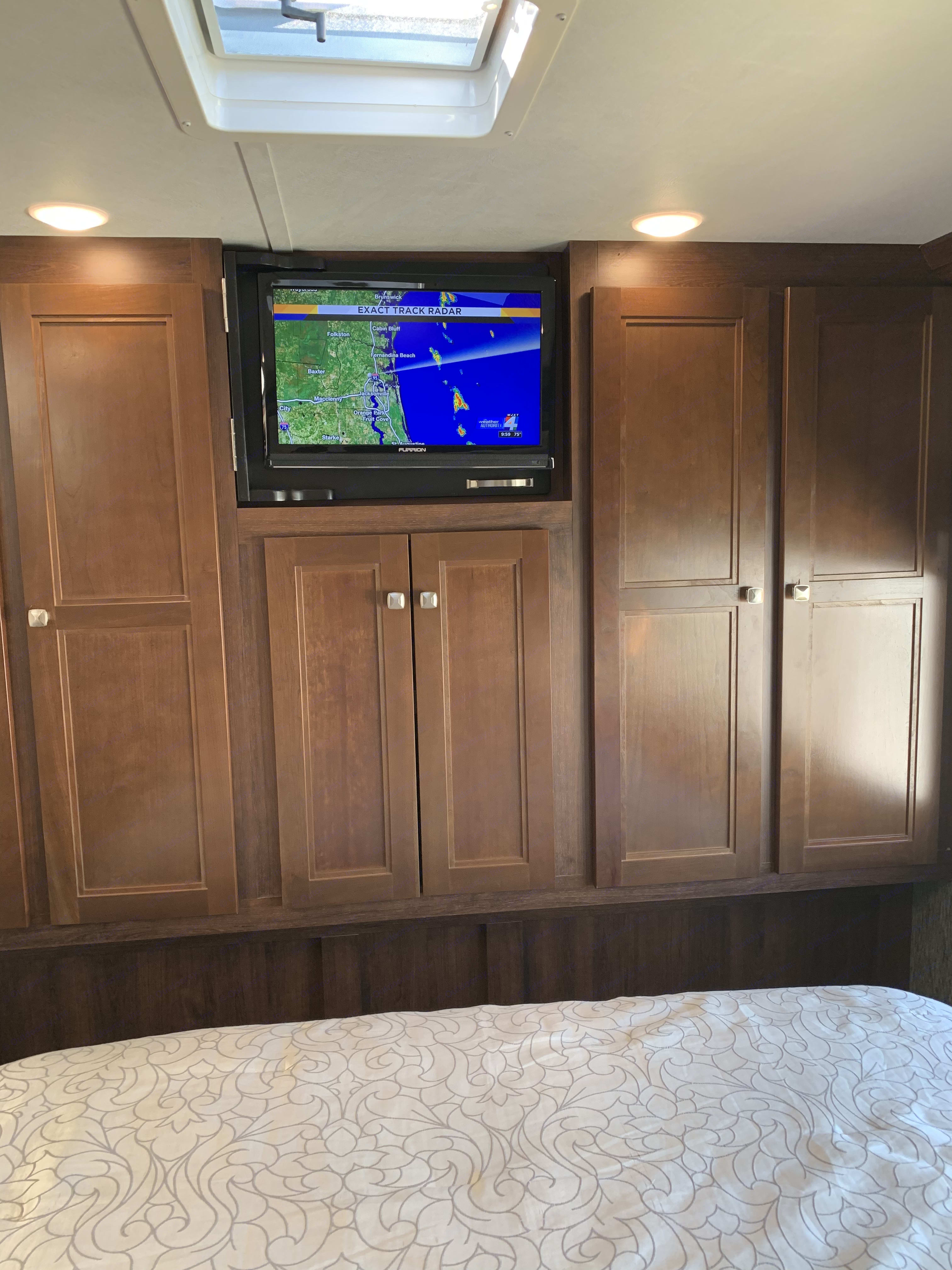 Master bedroom with LED HD TV with DVD player and plenty of storage space. Rustic cherry wood cabinets. . Forest River Sunseeker 2018