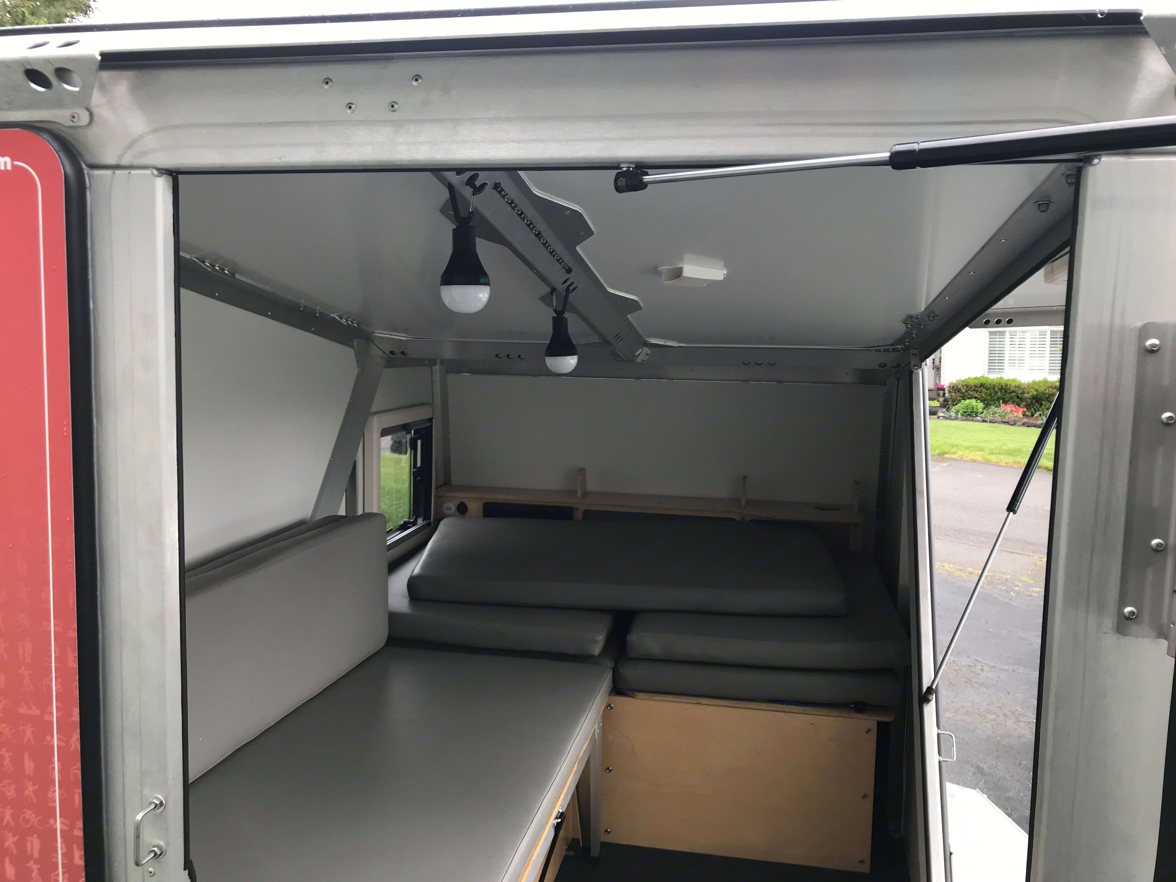 Interior has ample storage and multiple attach points. Couch pulls out to form sleeping area.. TAXA Outdoors Tigermoth Camper 2016