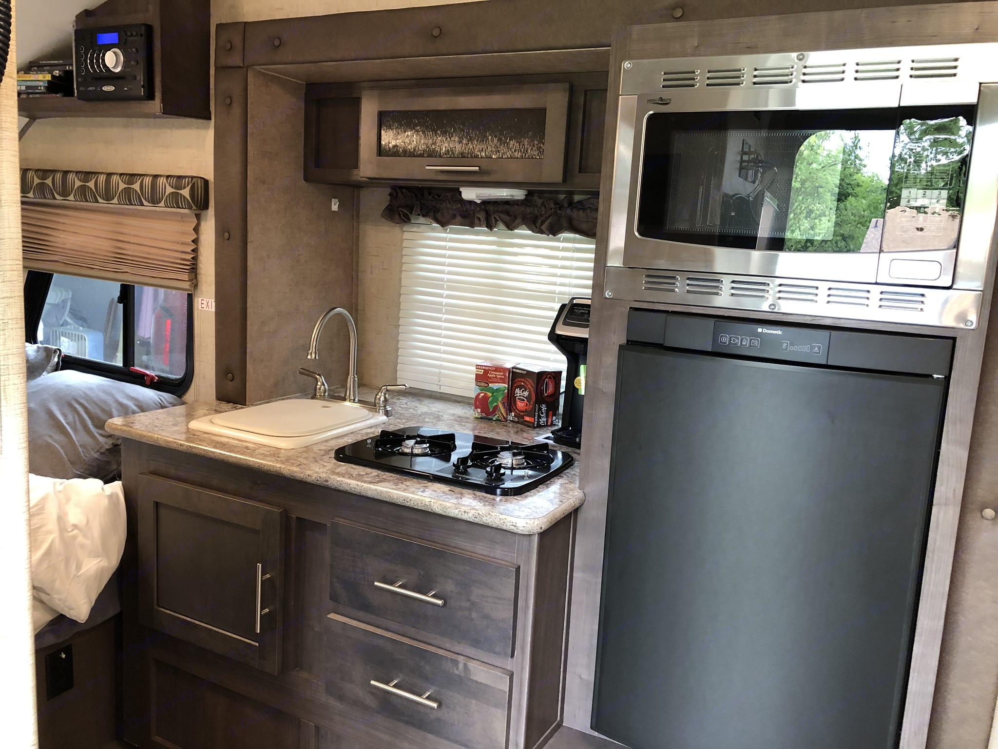 Sink, stovetop, fridge, and microwave oven. Forest River R-Pod 2016