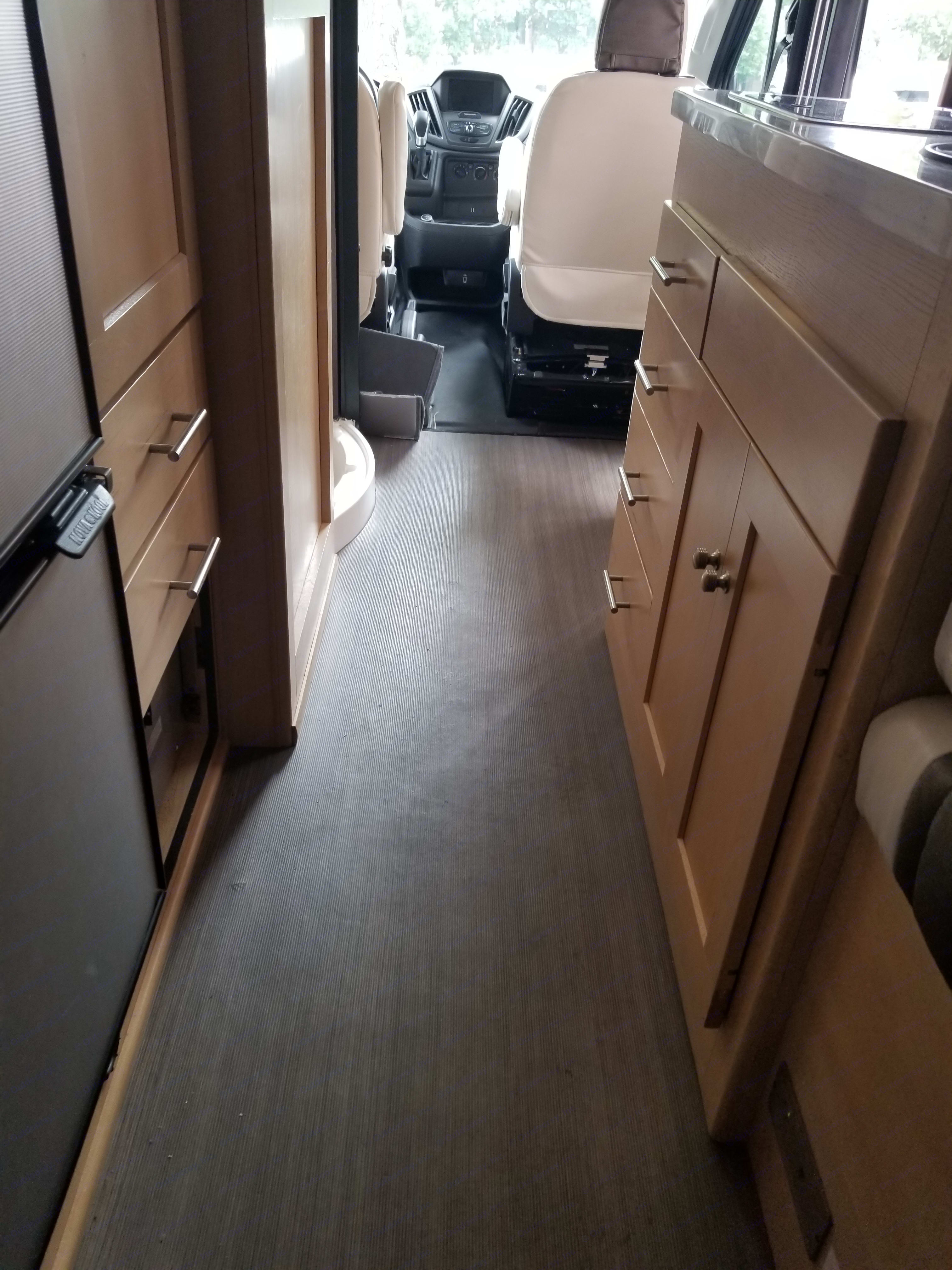 Standing at the rear of the RV looking towards the cockpit.  To the left is the fridge, wardrobe closet, and drawers for storage.  To the right is the kitchen area.. Winnebago Paseo 2017