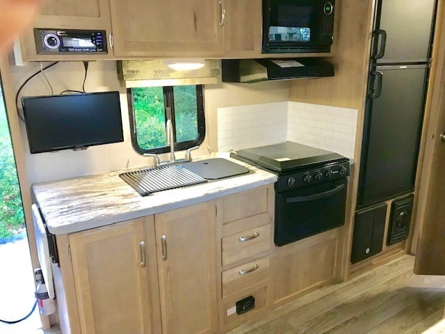 Full kitchen includes microwave, stovetop, oven, fridge, plates/bowls, flatware, and cups.. Winnebago Micro Minnie 2020