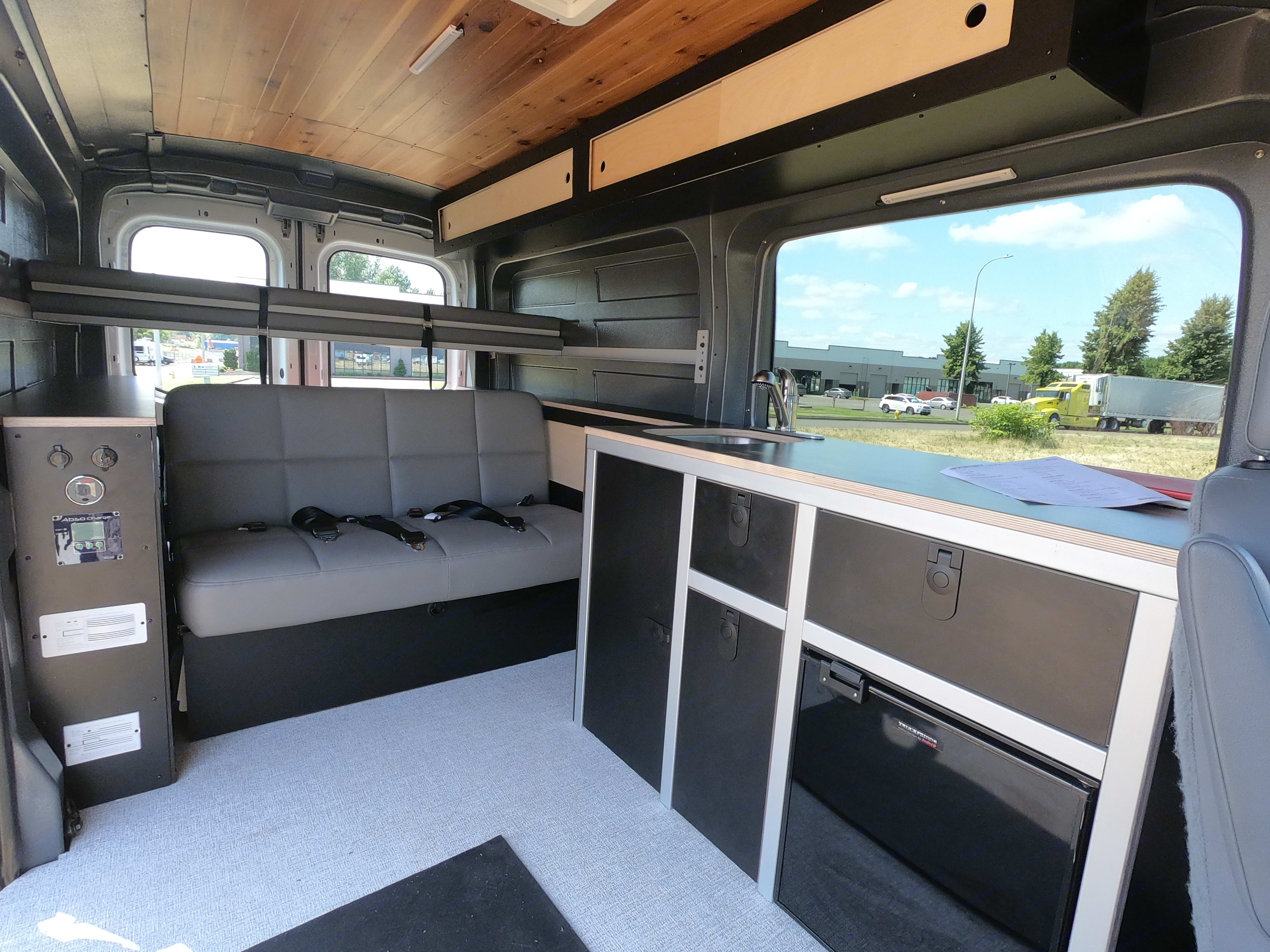 Interior view of bench seat with 3 seat belts and kitchen. Ford Transit 2018