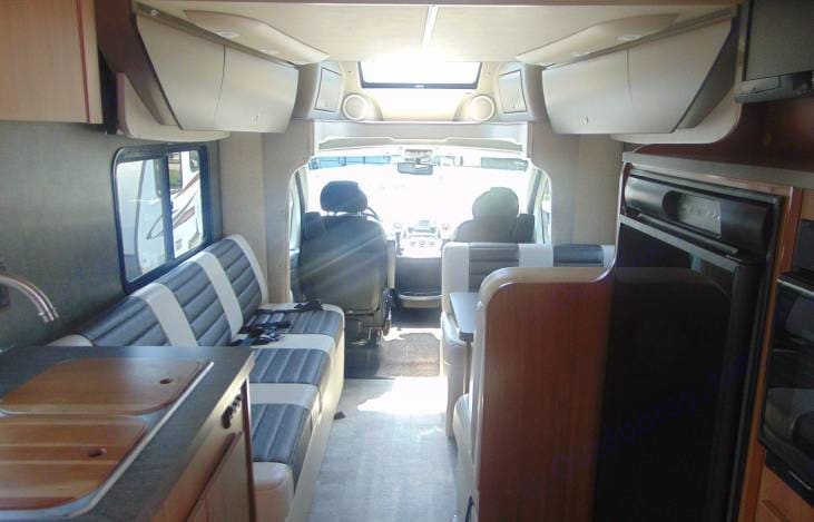 Table and couch fold down into separate small beds or join to form one giant bed (King). Winnebago Ithica Viva 2014