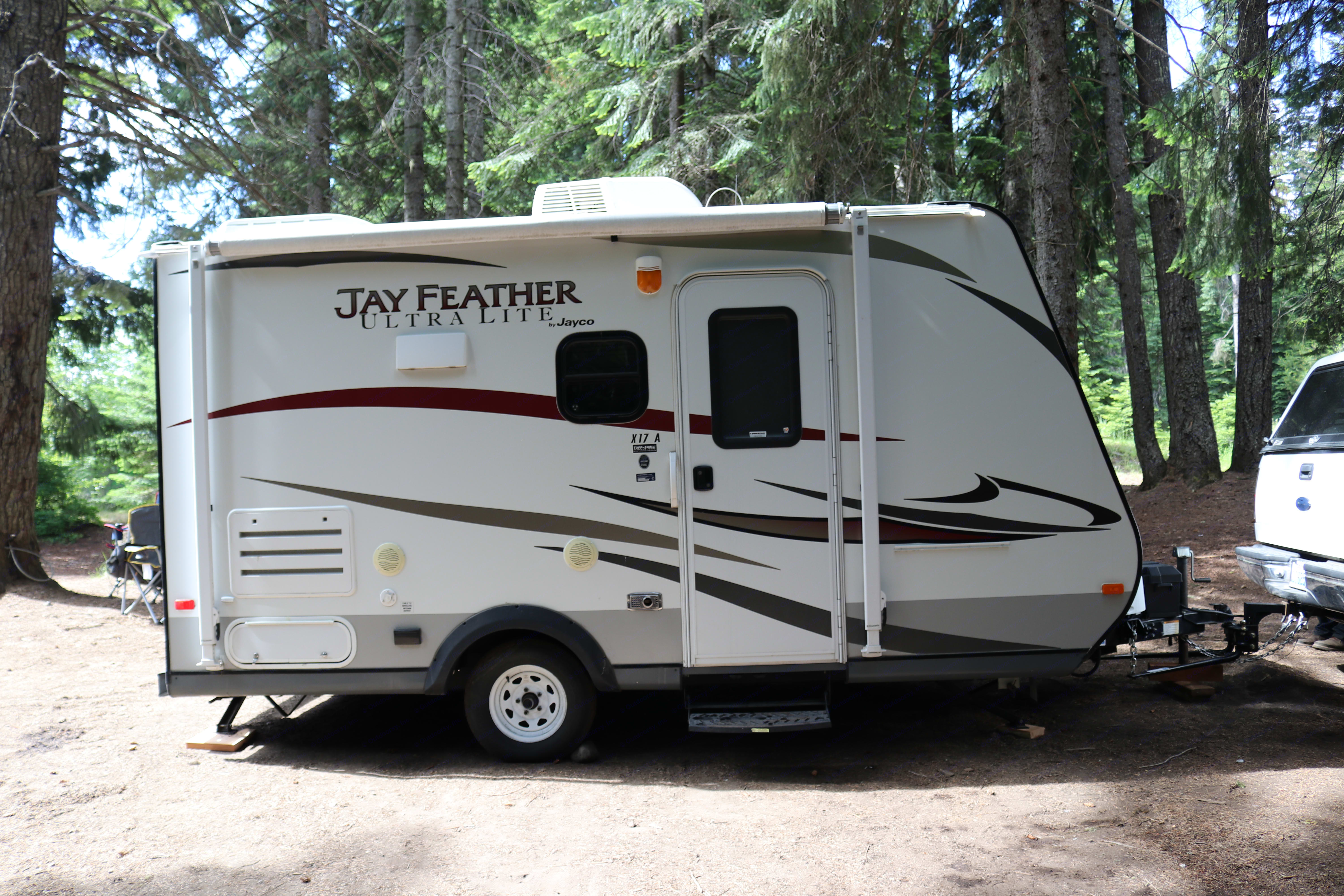 Showing this lightweight trailer with the hybrid beds in the front and back folded up for travel.  Also access to a small storage area in back.  Outside speakers connected to stereo inside.  Electrical Outlet for outside.  Cable/Satellite output.  Also usable awning. Jayco Jay Feather Ultra Lite 2013