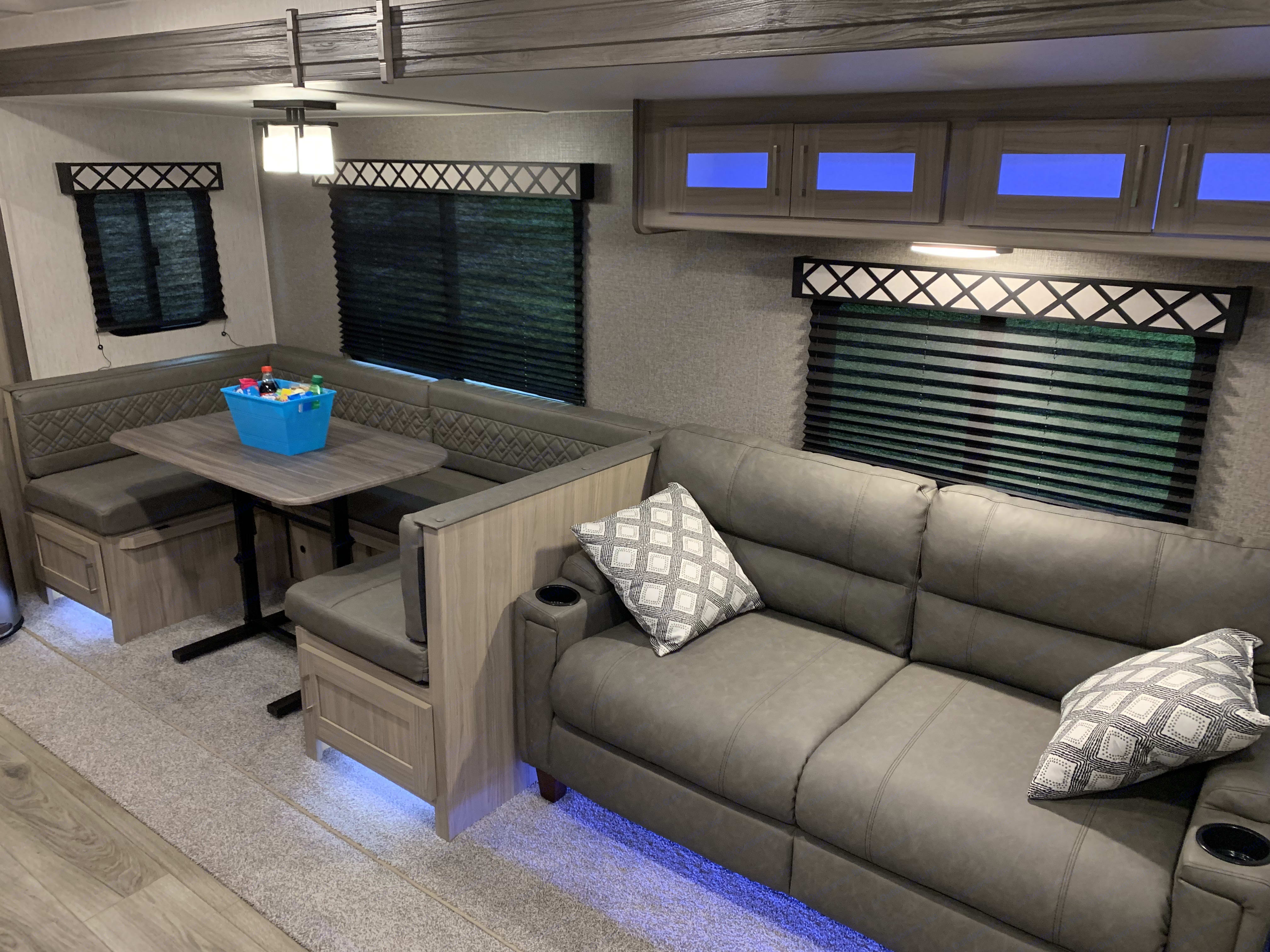 Living room area with a large sleeper sofa and U-shaped dinette.. Coachmen Freedom Express 2020