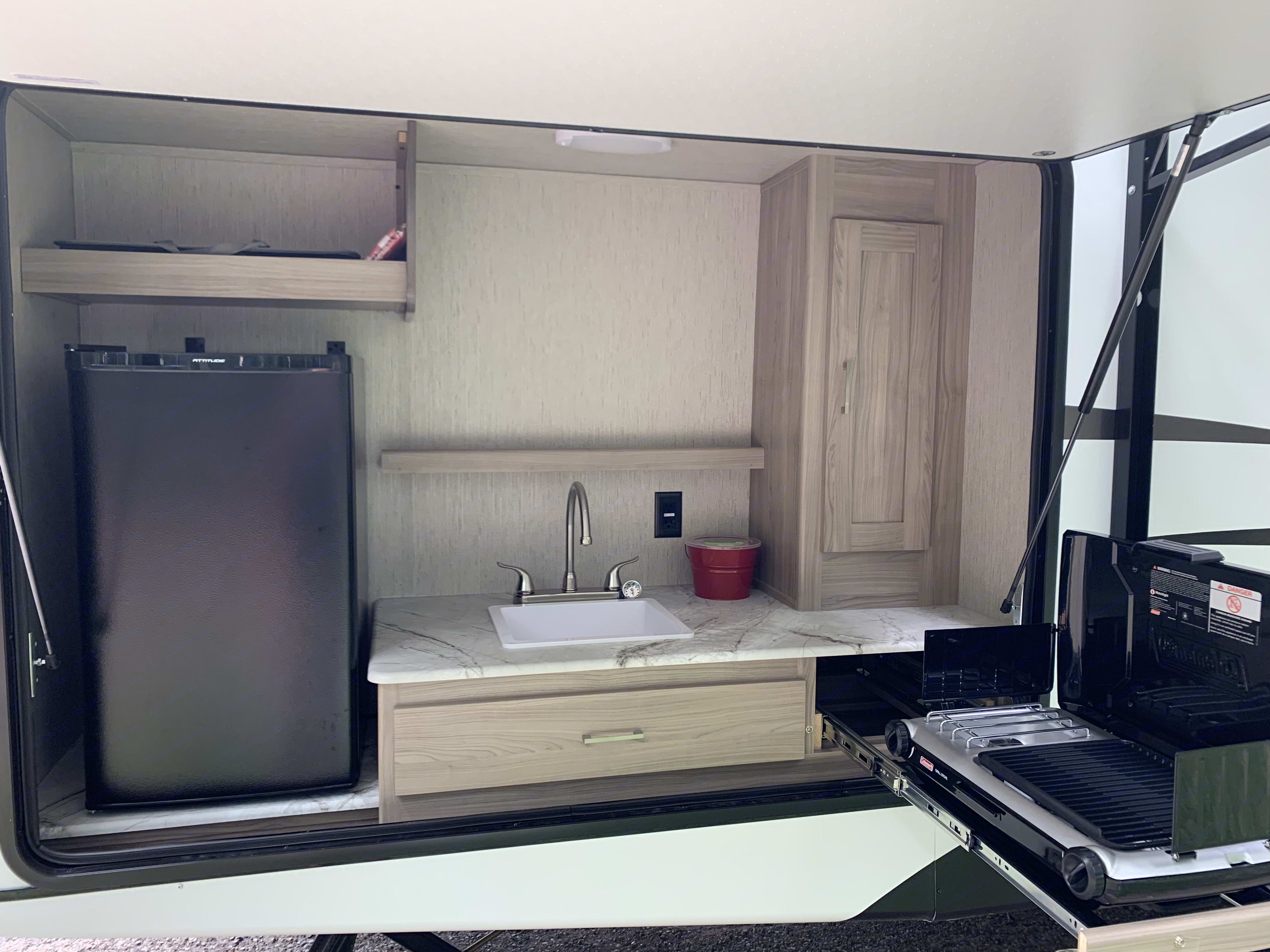 Outdoor kitchen with mini-fridge, sink, and gas grill.. Coachmen Freedom Express 2020