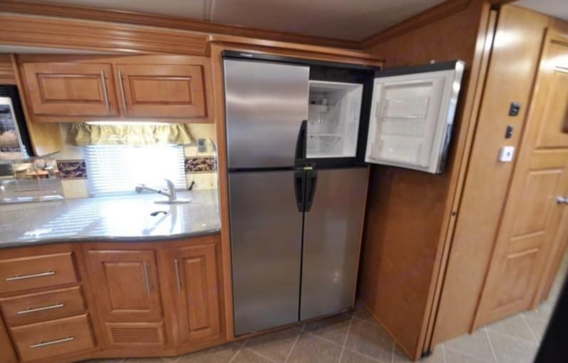 Check out this 4 door stainless fridge! Huge, also runs off propane so it will keep everything cool while driving and the second you connect to the power at a camp site it change to electric. Fantasy right? I love it! . Forest River Cross Country 2011