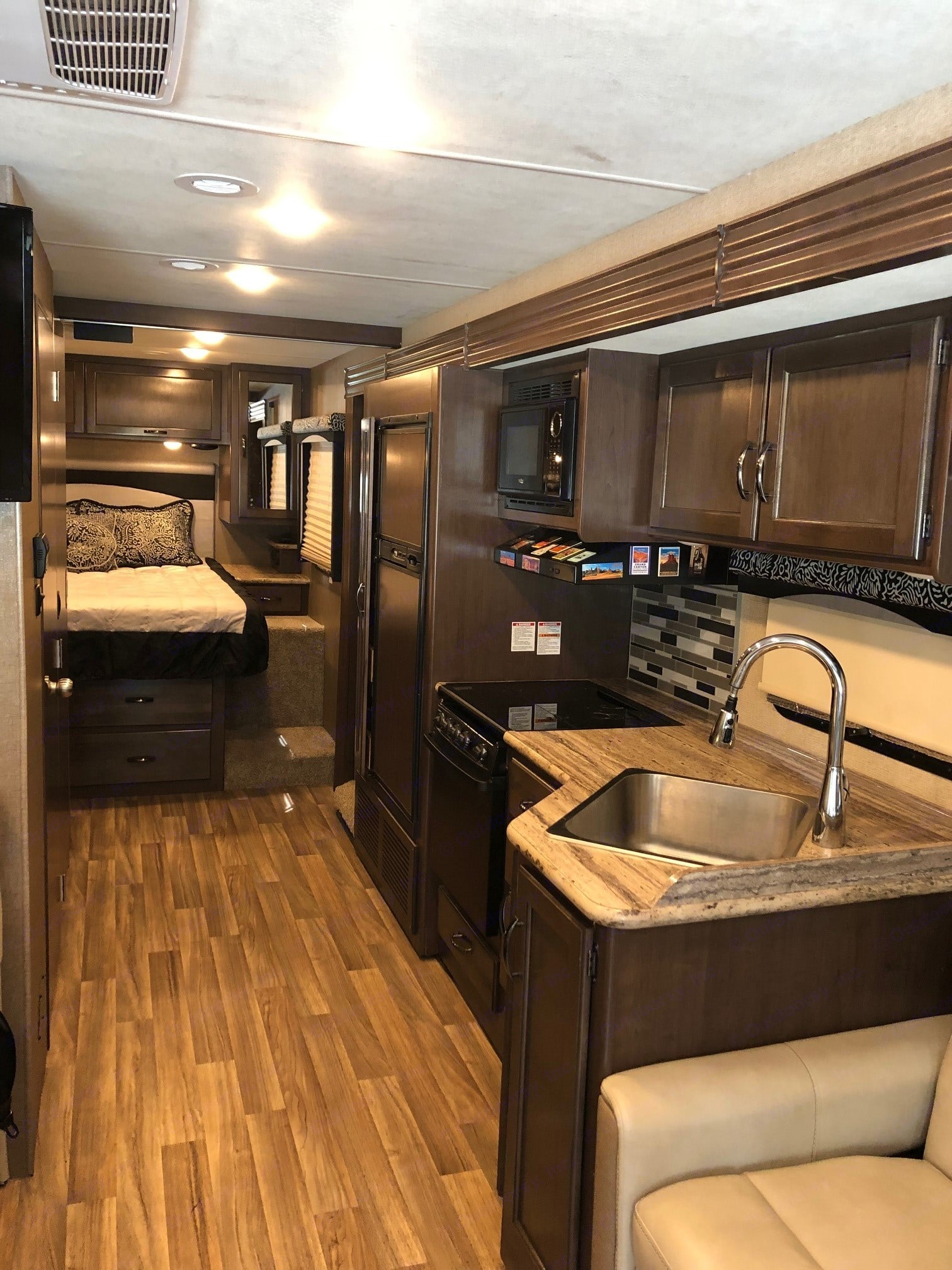 Interior view of coach with wall slide out. Comfortably spacious, similar to a small apartment - that you can drive! This view shows kitchen including refrigerator and microwave, plenty of storage/cabinet space, and the master bedroom at the rear of the coach.. Thor Motor Coach A.C.E 2018