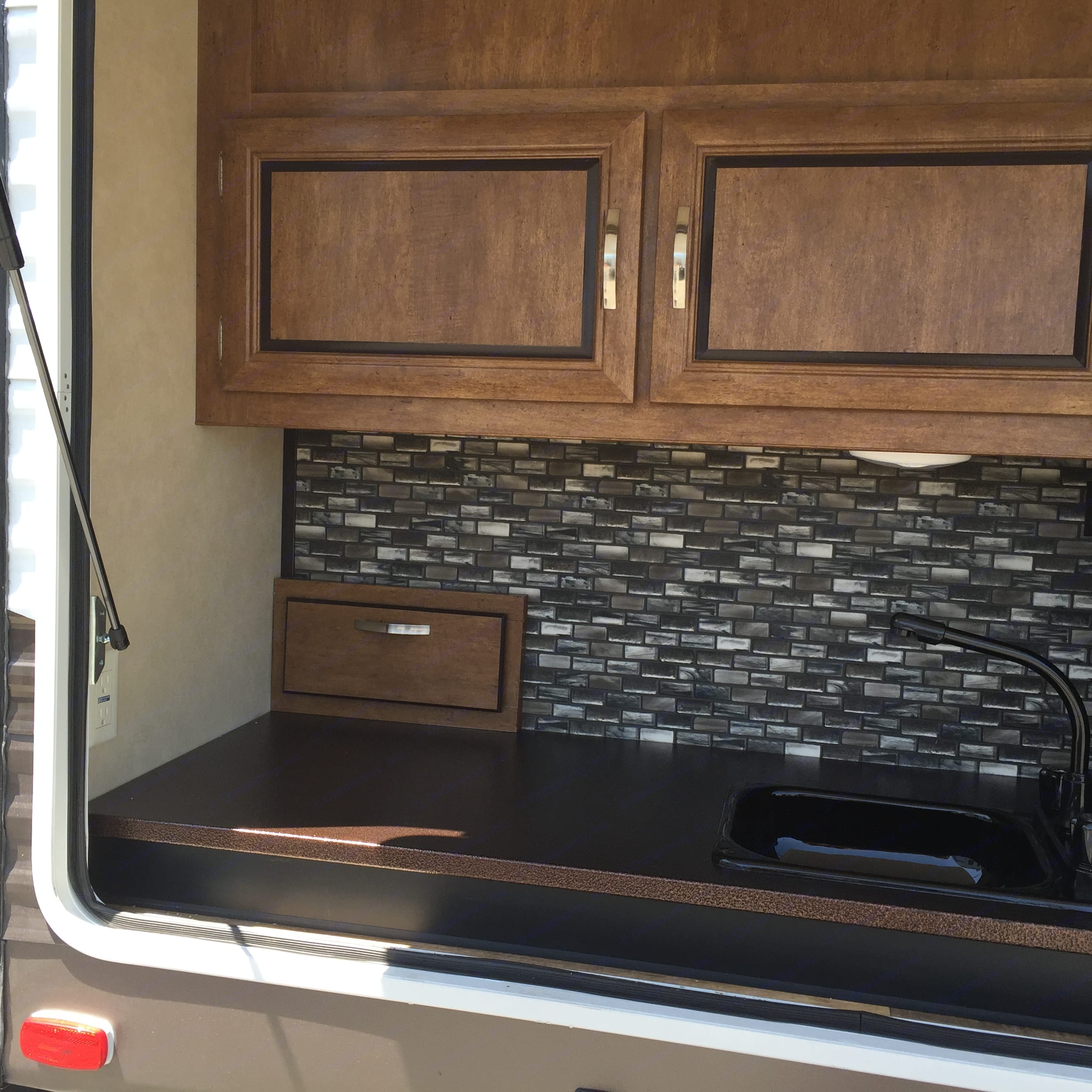 Outdoor kitchen with a refrigerator, sink, gas grill and cabinets.. Forest River Wildwood 2017