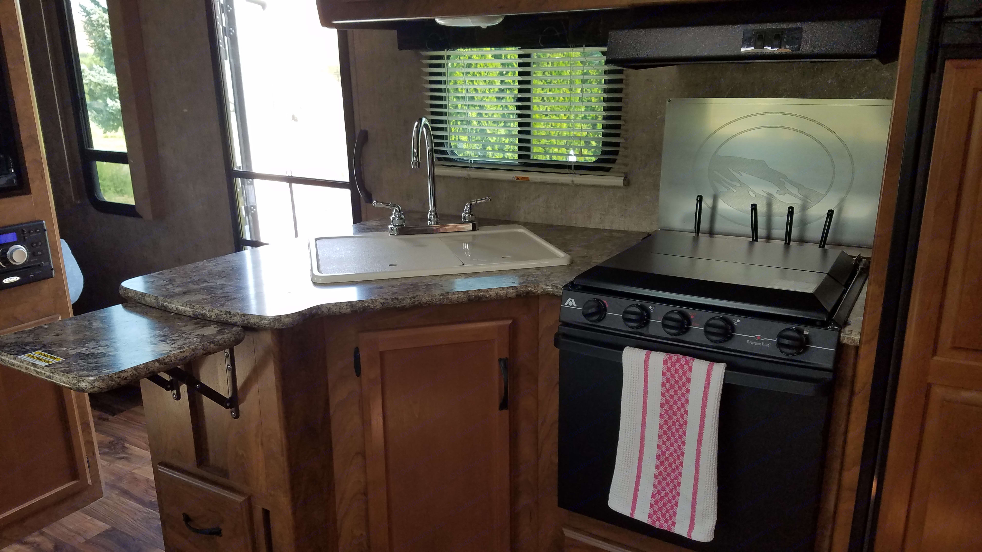 Kitchen with double sink, gas range, gas oven, microwave, and extra large fridge with freezer.. Outdoors Rv Manufacturing Creek Side 23DBS 2017