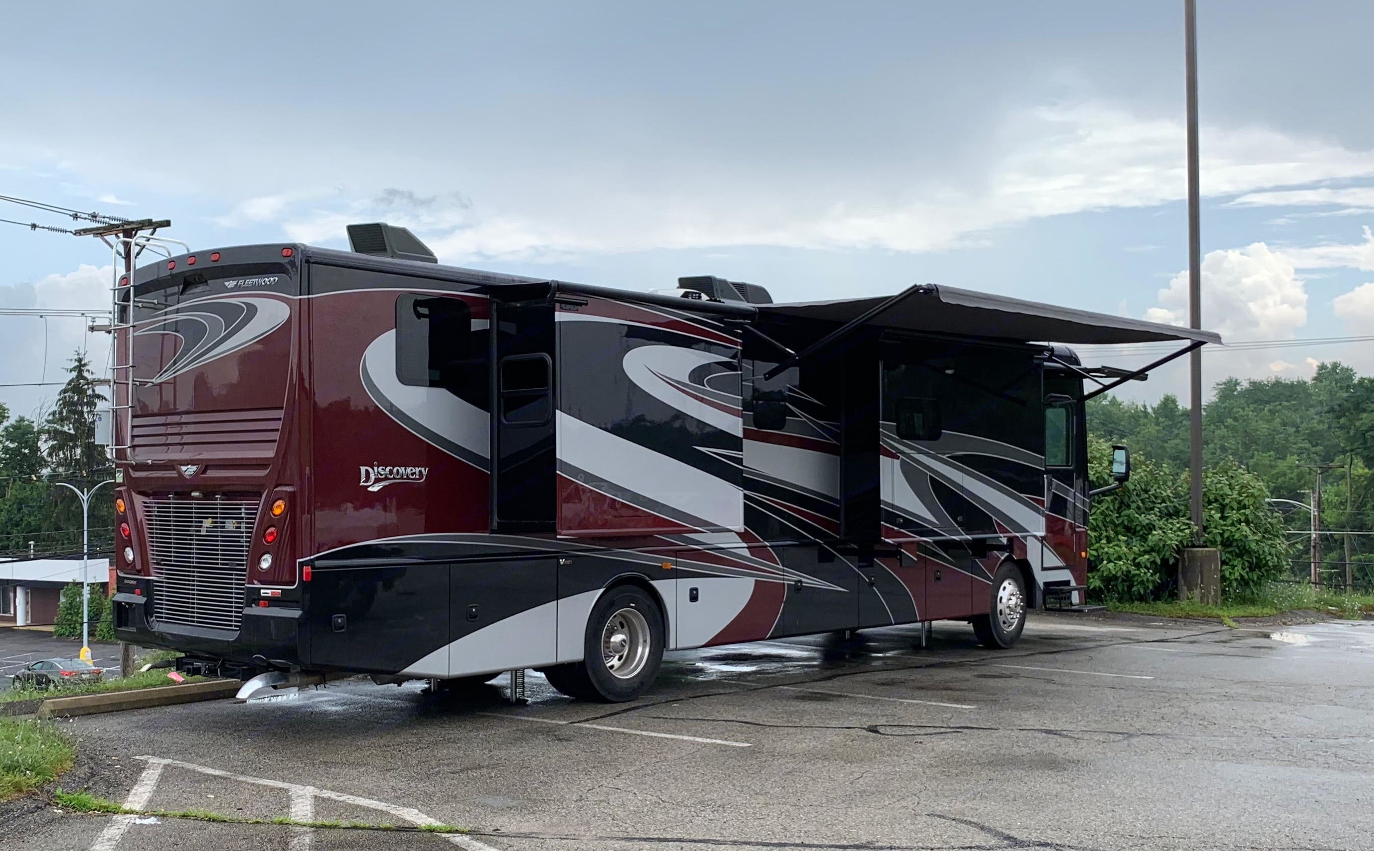 Exterior has lighted awnings and exterior entertainment center. Fleetwood Discovery 2019