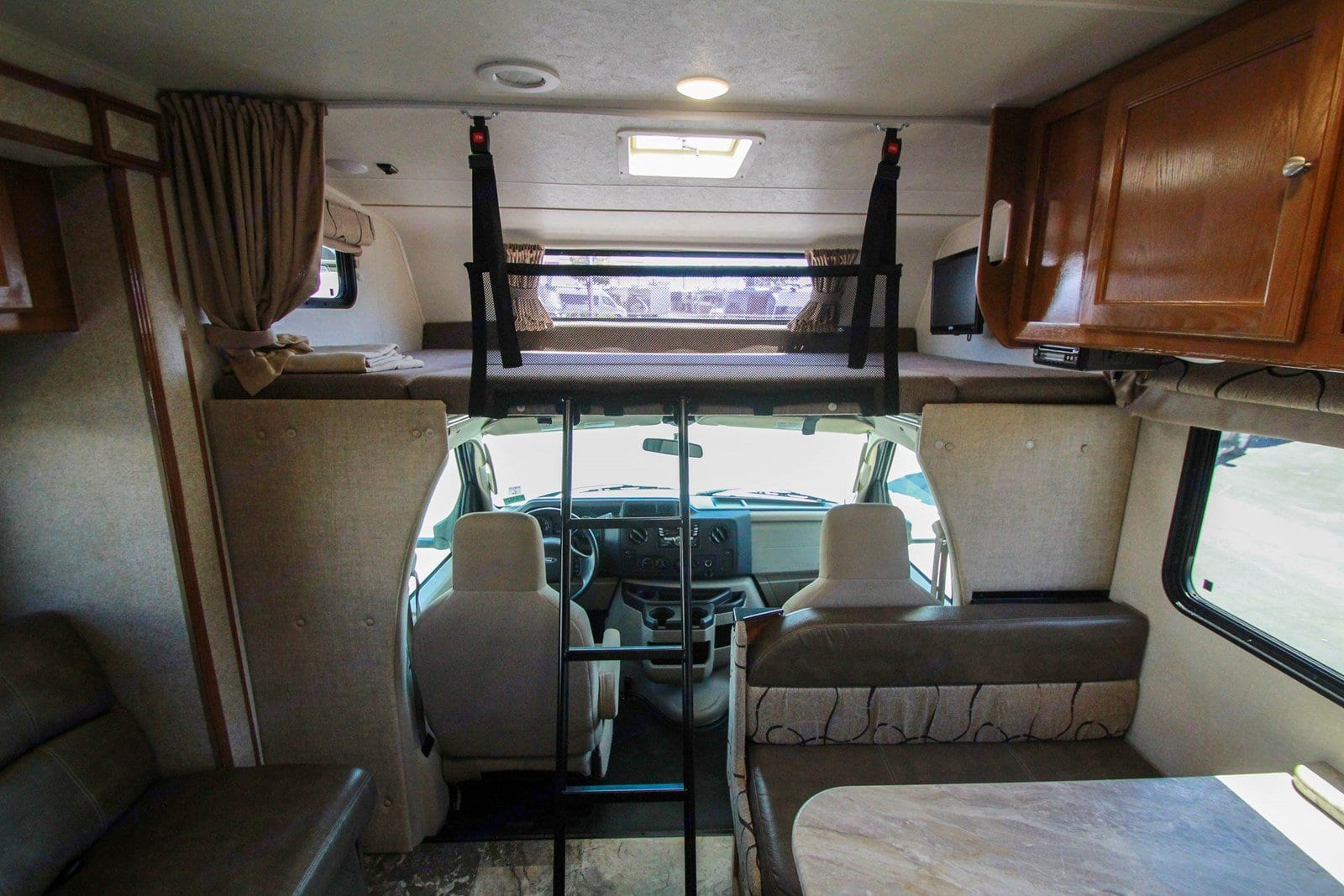 Bunk over cab sleeping area is larger than a queen bed, with safety net for those that toss and turn in their sleep (ladder for access not shown). Part of mattress can be removed for extra headroom while driving.. Coachmen Leprechaun 2019