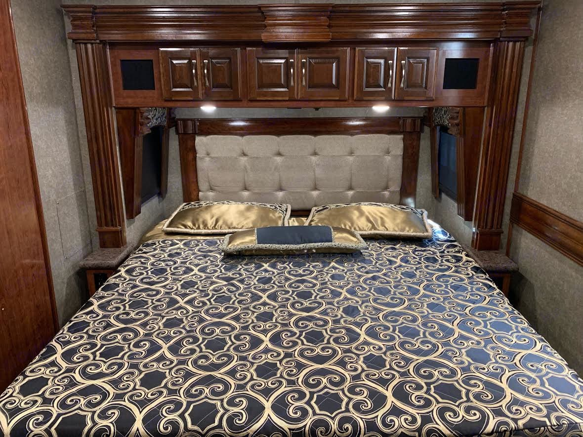 Master king bed with controls for lights, generator, or exterior cameras.. Fleetwood Discovery 2019