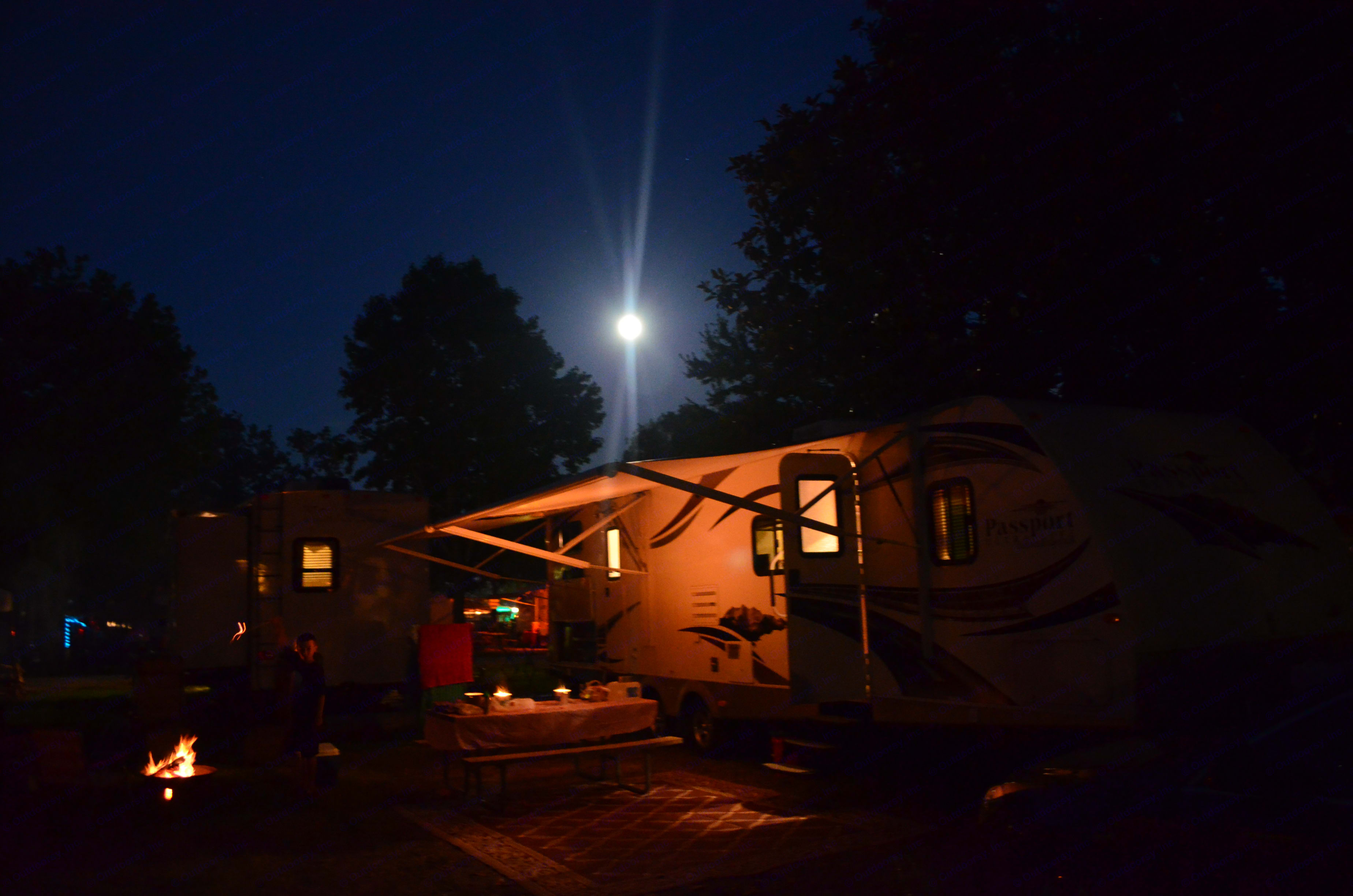 The trailer lit up with the main house light under a super moon.. Keystone Passport 2011