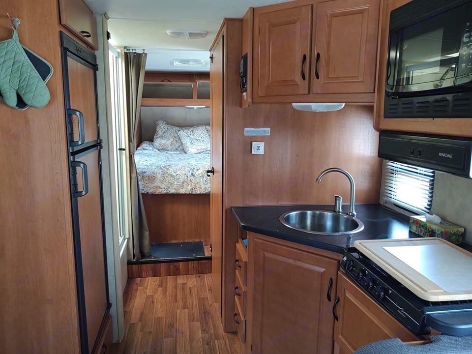 Kitchen with image of bedroom in back. Has a curtain for privacy. . Thor Motor Coach Four Winds Majestic 2013