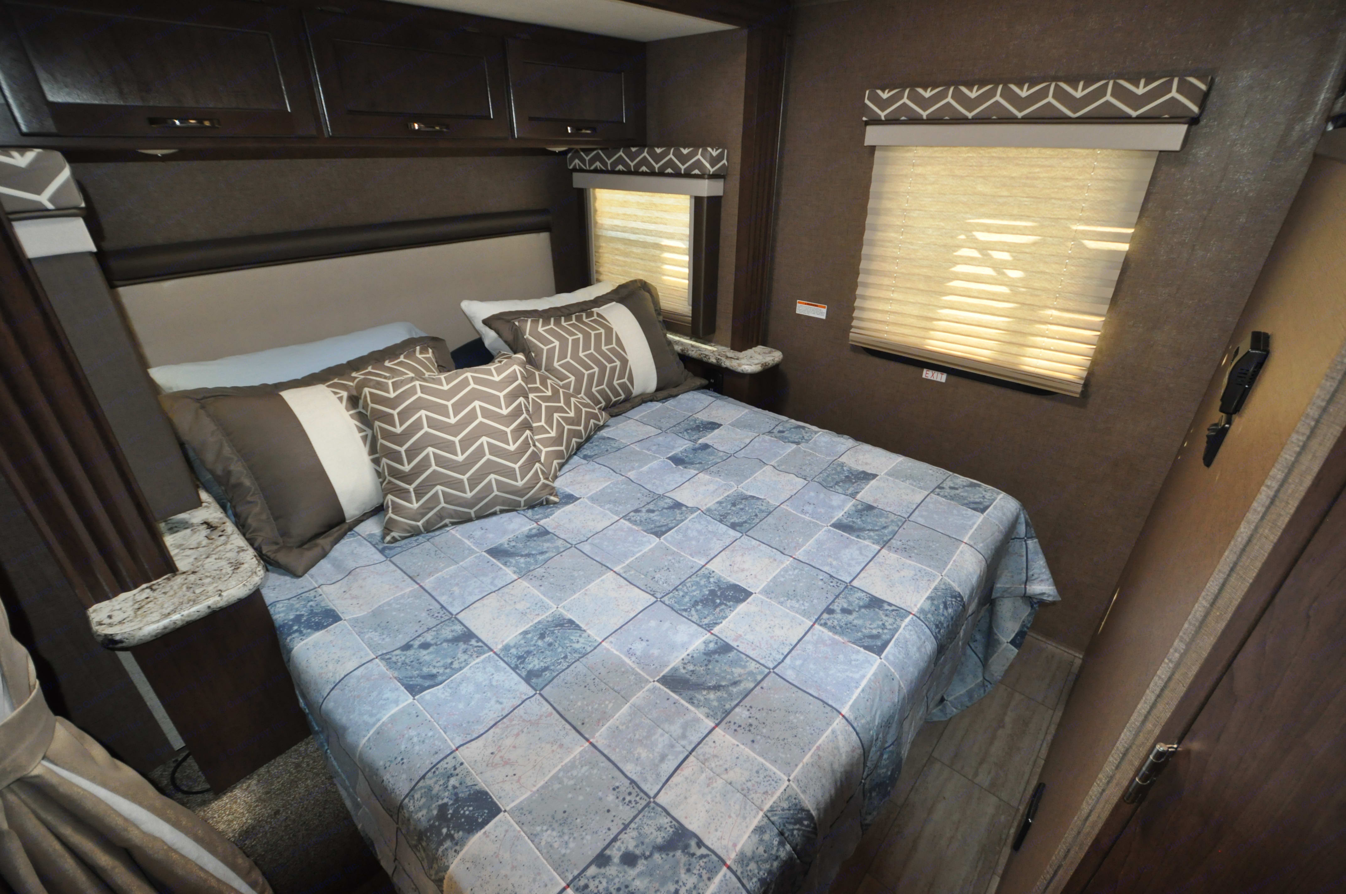 Queen size bed with overhead lighting and storage.. Thor Motor Coach A.C.E 2019
